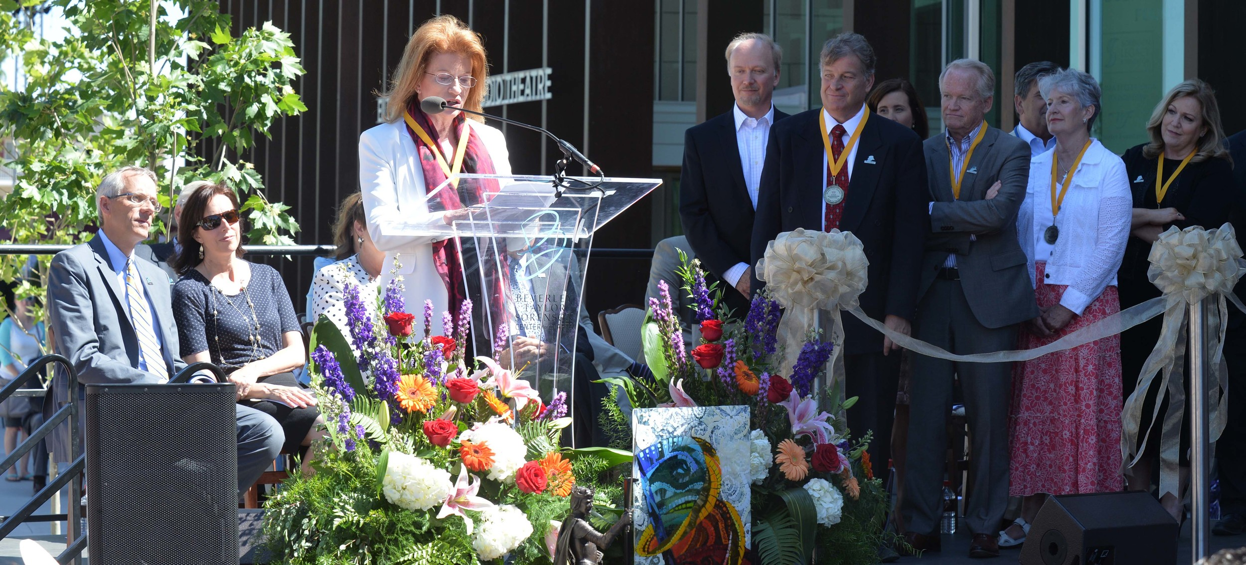 Ann Crocker, representing the Sorenson family and the Sorenson Legacy Foundation, addresses the crowd as members of the Sorenson family look on at the dedication of the Beverley Taylor Sorenson Center for the Arts.