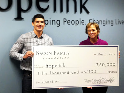 Tony Bacon of the Bacon Family Foundation presents a check to Hopelink CEO Marilyn Mason-Plunkett