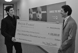 Tony Bacon presents a check to United Way CEO Jon Fine to help launch the Parent Child Home Visit Program on the Eastside.