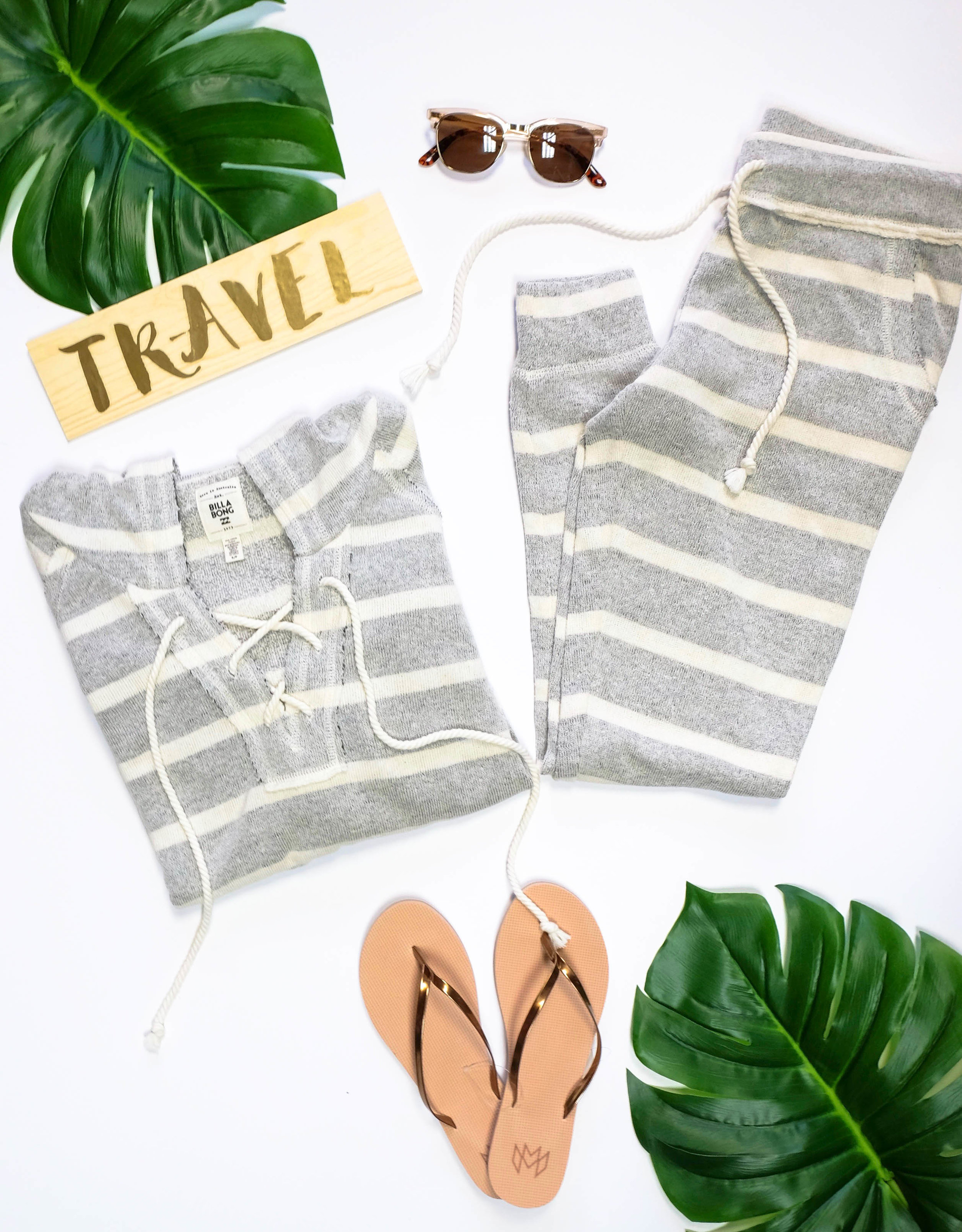 """For our ladies, a comfy day-of-travel outfit is necessary without looking like you just rolled out of bed for your 5 AM flight (even if you did!). Pairing your favorite sweatshirt and sweatpants doesn't always have to be your """"day off look"""", especially with this cute Billabong set, an effortless way to look presentable. Now for shoes… I would personally wear some easy sandals to slip on and off because who wants to spend any more extra time in airport security?! Plus, I like to take my kicks off on the plane and can save myself the embarrassment of stinky shoes. (Quick Tip: Keep a pair of Stance socks in your carry on!) And don't worry, we added some Toms sunglasses to hide those bags under your eyes. ;)     Pictured:  Billabong Sweatshirt  Billabong Sweats  Toms Sunglasses  Malvados Flip-Flips      Now for the part I know everyone has been dreading since Thanksgiving.  Swimsuit Season .Trust me, the last thing I want to do is put a swimsuit on my terrifyingly white body too. But we have so many cute suits in store that its hard to not want to buy them! My current swimsuit obsession is this fun, printed Maaji two-piece. Also, they're swimwear is reversible so it's basically getting two swimsuits in one! Which means you won't have to pack as much and your suitcase will have more room for shoes :) Other than a swimsuit being a beach/pool day essential having a cute towel will make getting that sun burn a little cuter. You cant't go wrong with this Volcom 'Hypnotize' Round Towel, its even big enough for two (AKA another reason to pack more shoes)! Last but not least, don't forget to support your favorite local boutique and pick up a cute and functional Vanilla Mizu water bottle to keep your choice of beverage cold all day! Post a pic and tag us on Instagram of where you and your Vanilla bottle are vacationing to this Spring!"""