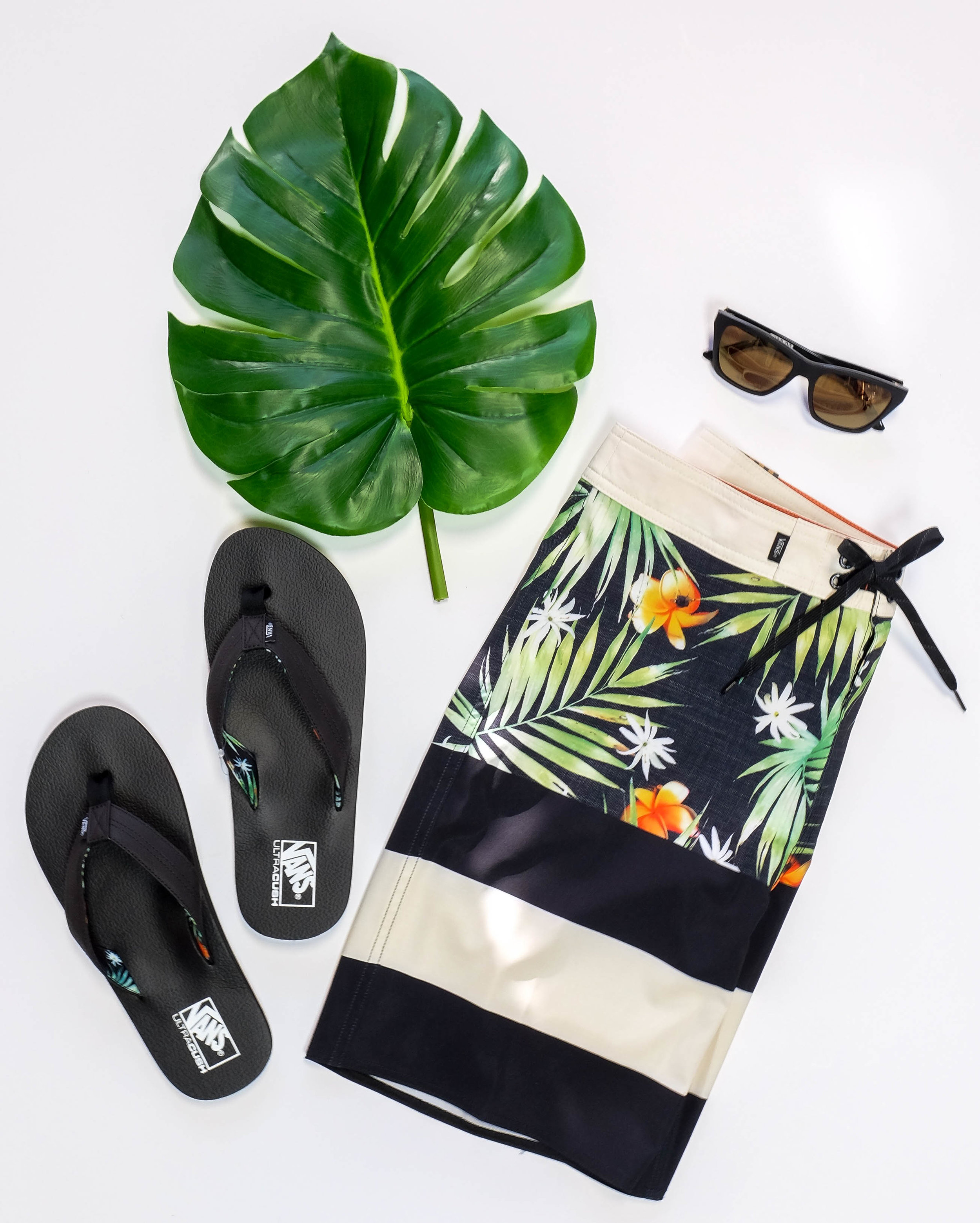 Pictured:  Vans Boardshorts  Vans Flip Flops  Von Zipper Sunglasses  Now guys we know you're just as picky as us when it comes to clothes. This outfit might not be every guys cup of tea but just take a second to look at how rad this Dark Seas button-up is. You can't deny that the subtle rose pattern isn't something you might want to wear on a night out on vacay. Pairing it with popular style, RVCA shorts and pop of red with some Old Skool Vans wouldn't be a bad idea either. Just saying boys, this is something we'd like to see you in ;)