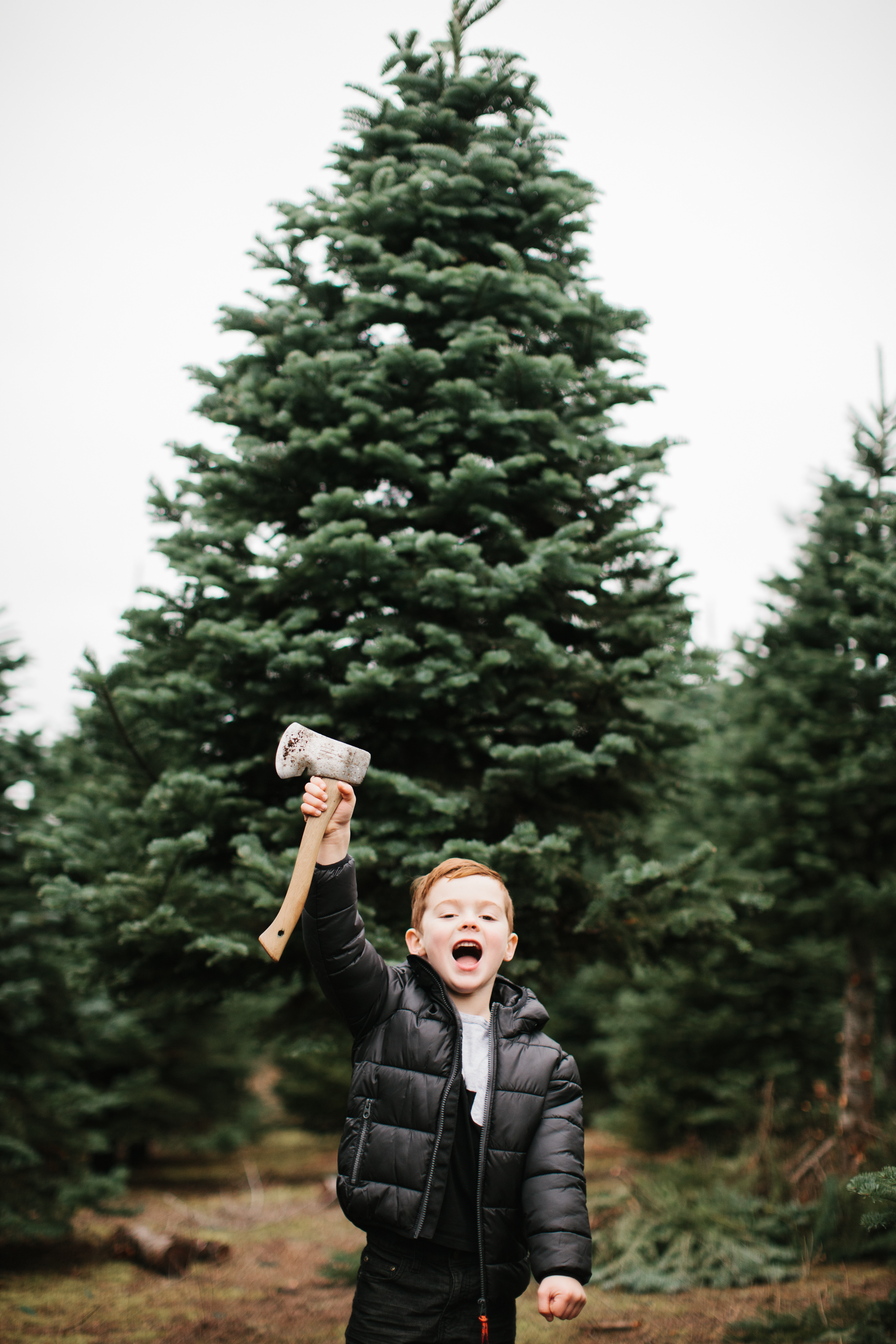 young boy holding up axe