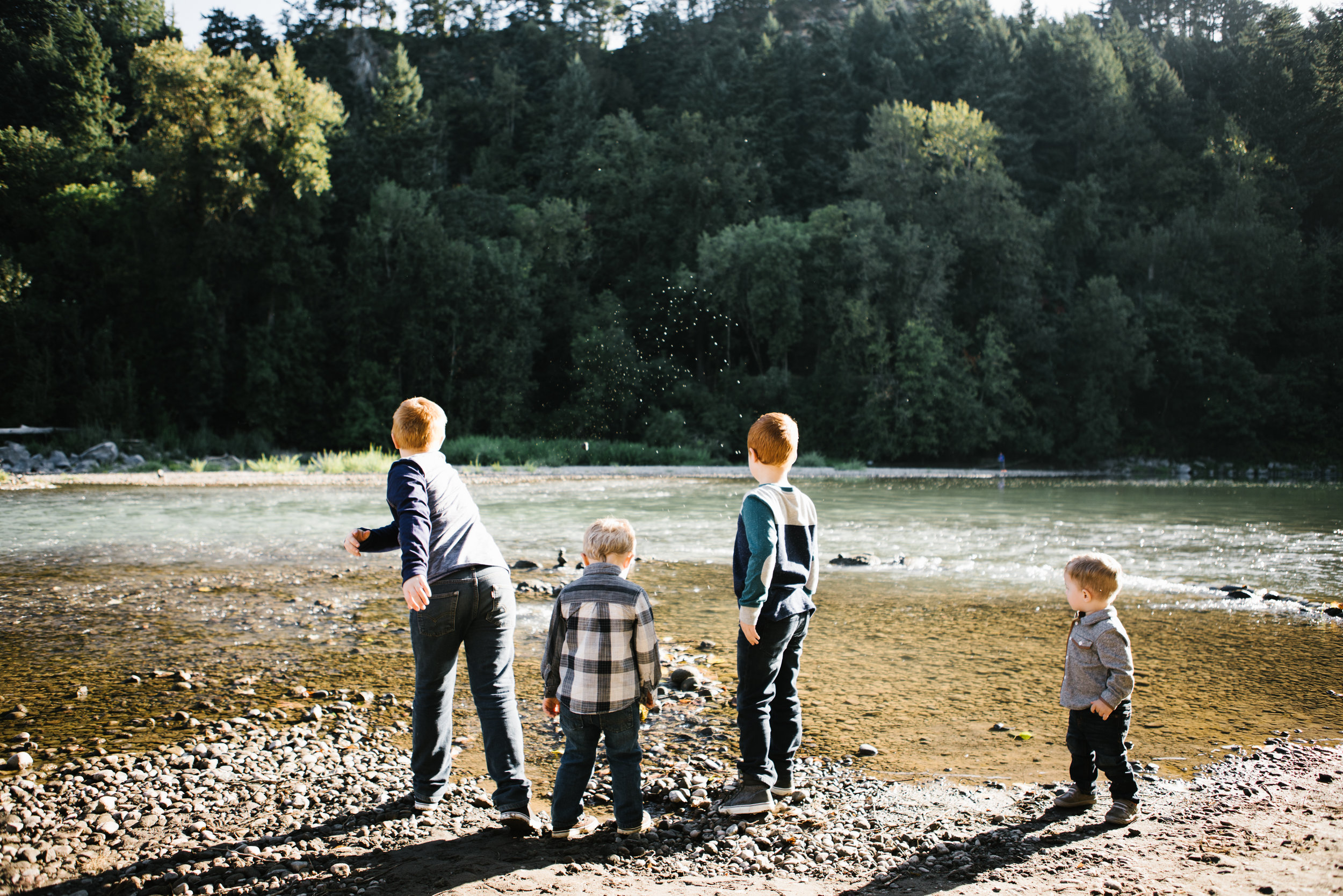 Four young brothers playing by river