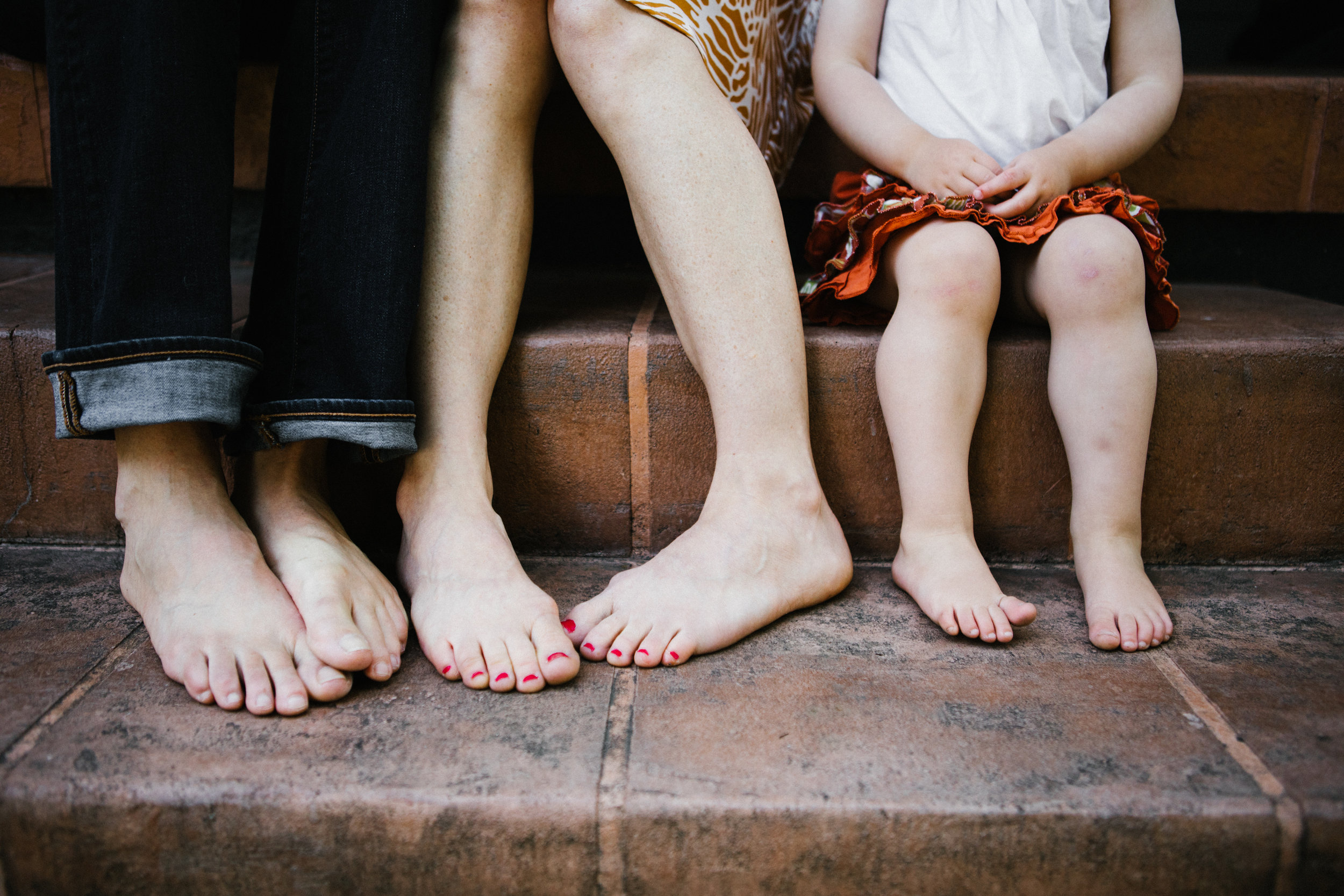 Family of three's feet on porch