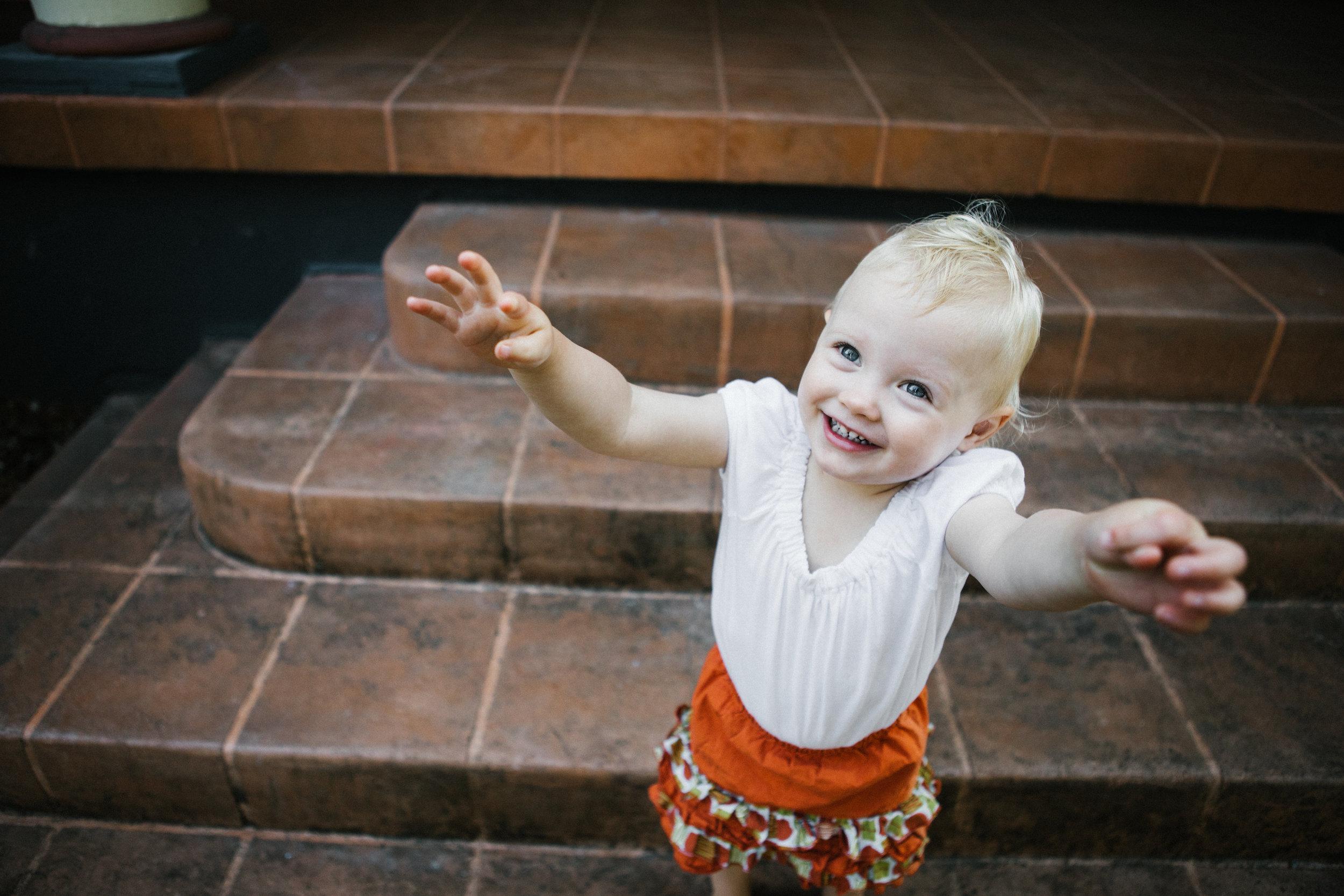 Toddler girl reaching up