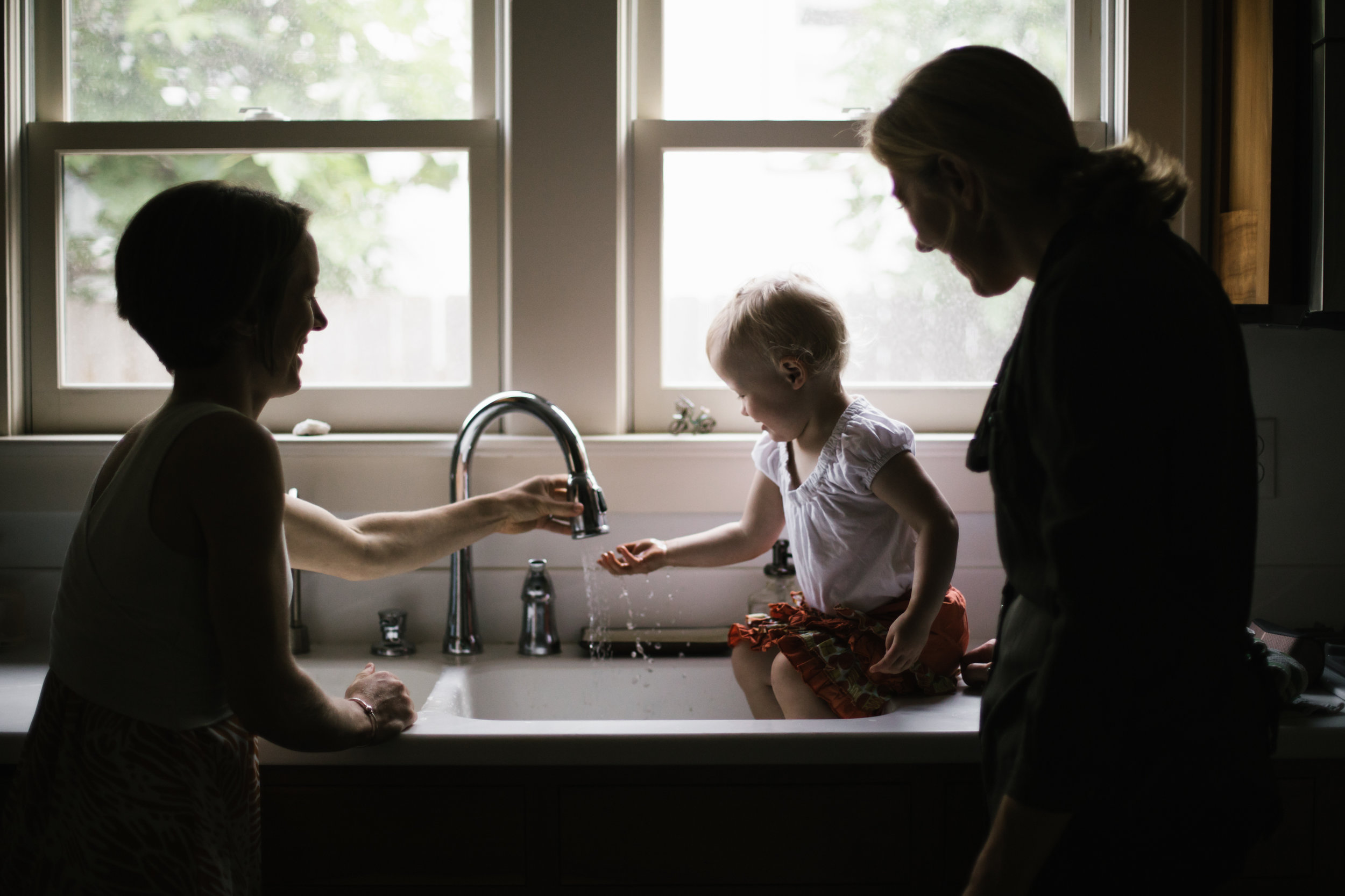 family of three playing in sink