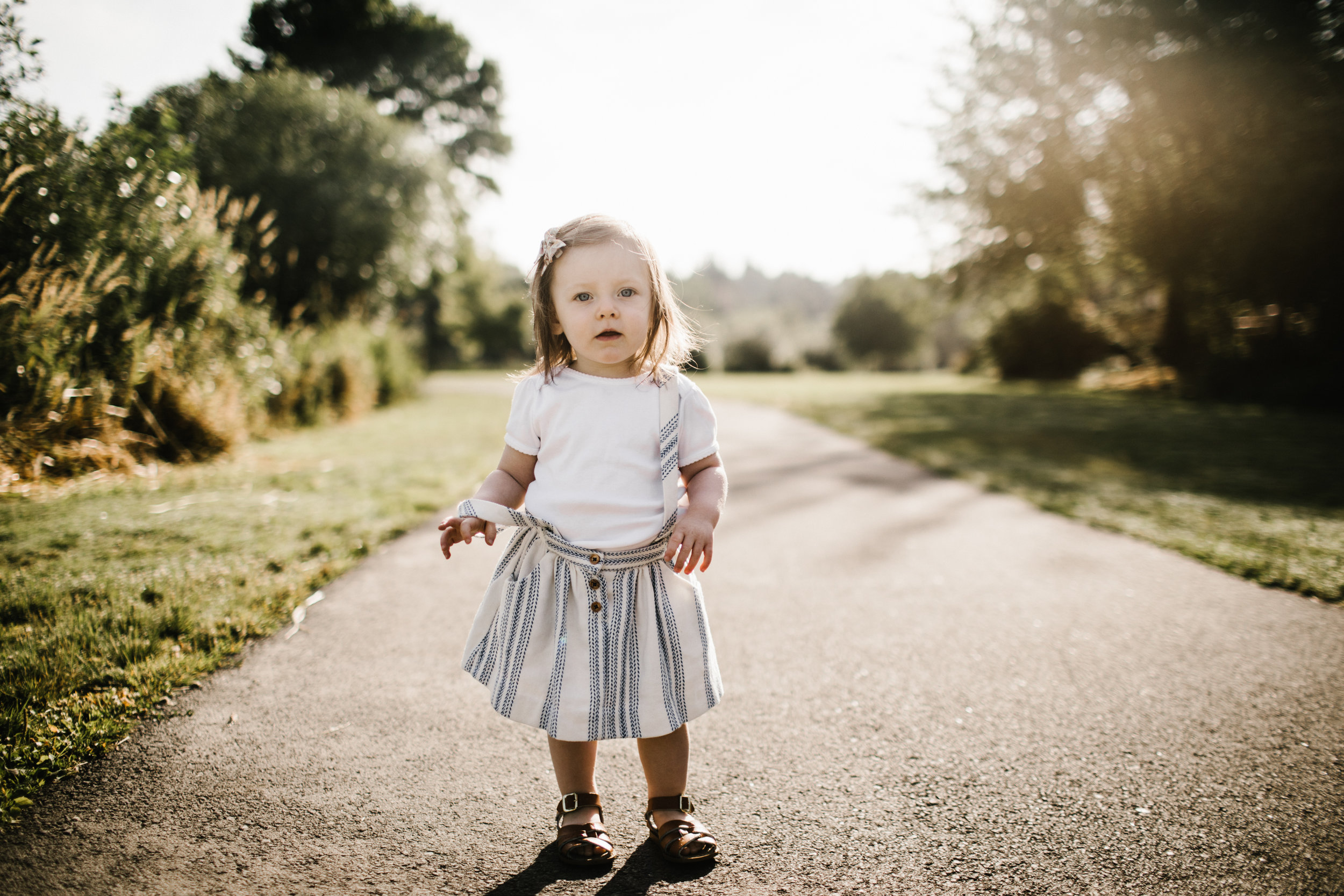 Toddler girl on path looking at camera