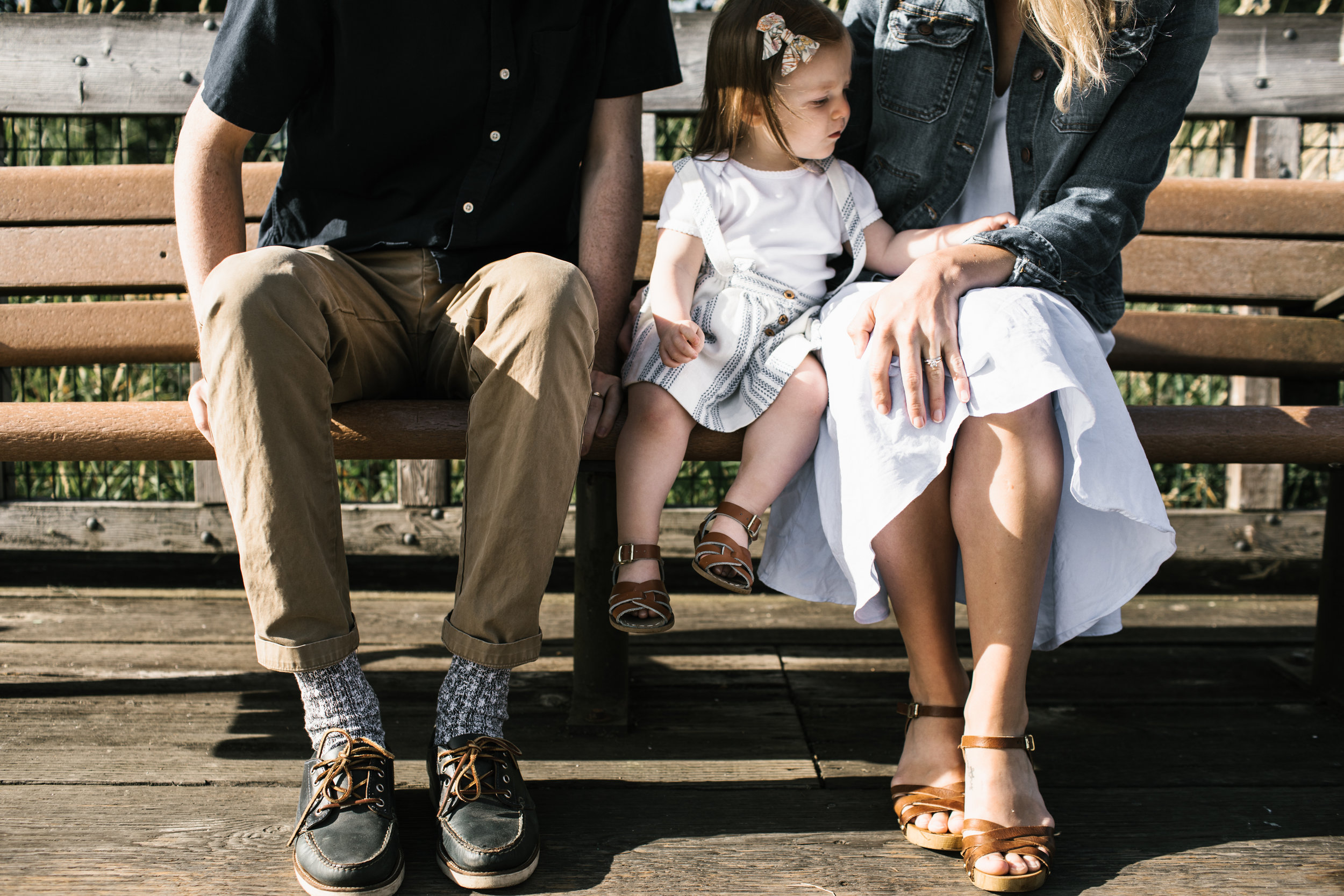 family of three sitting on bench