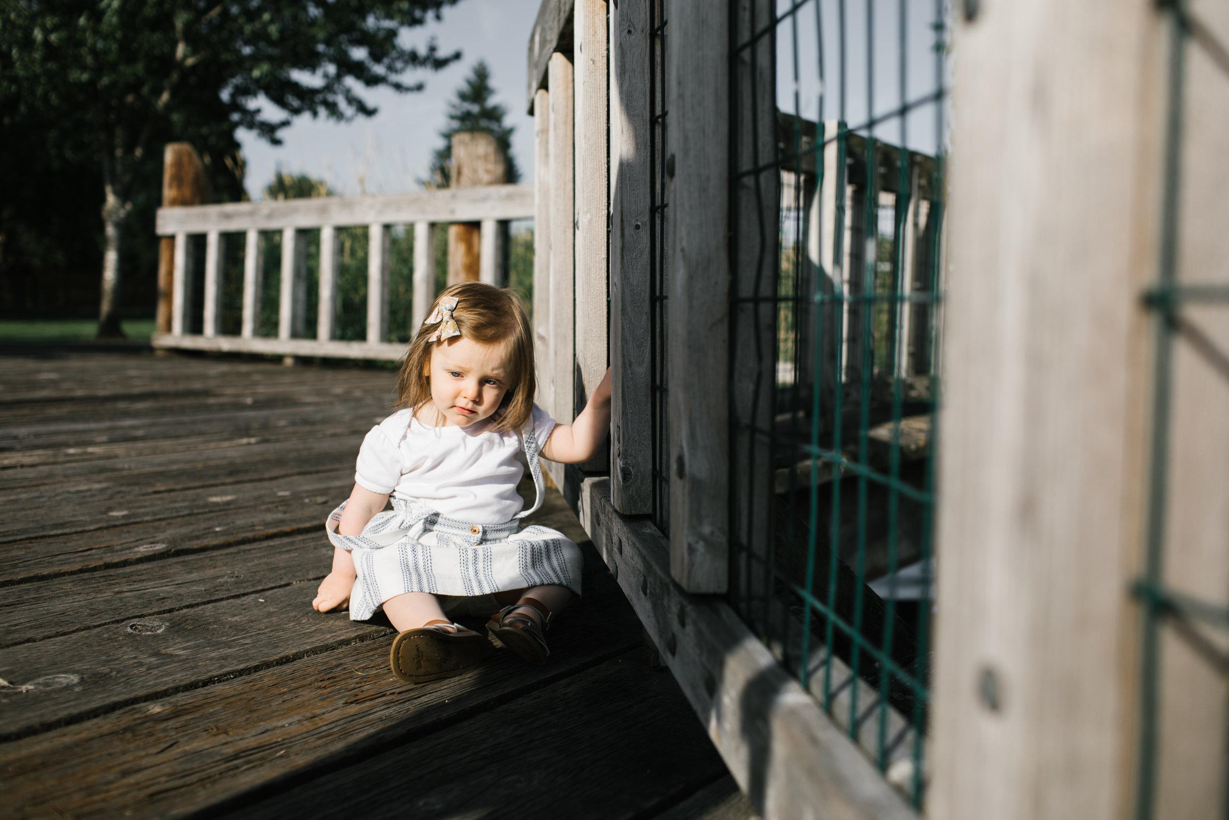 Toddler sitting on wood bridge