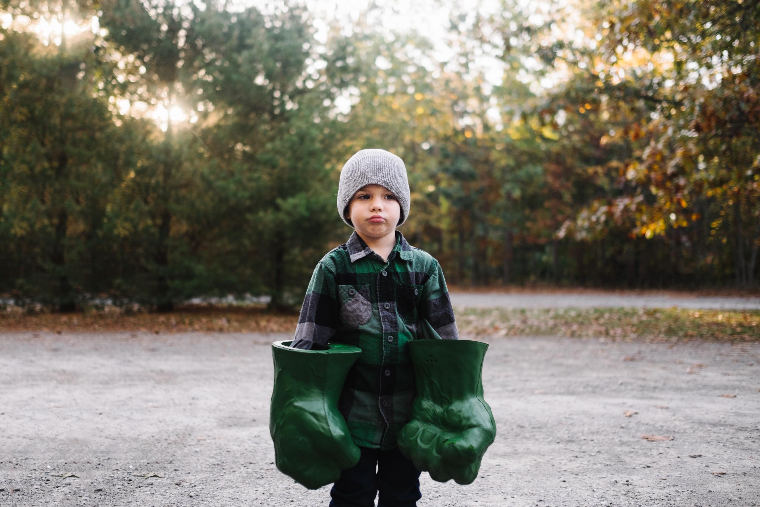 young boy wearing hulk hands