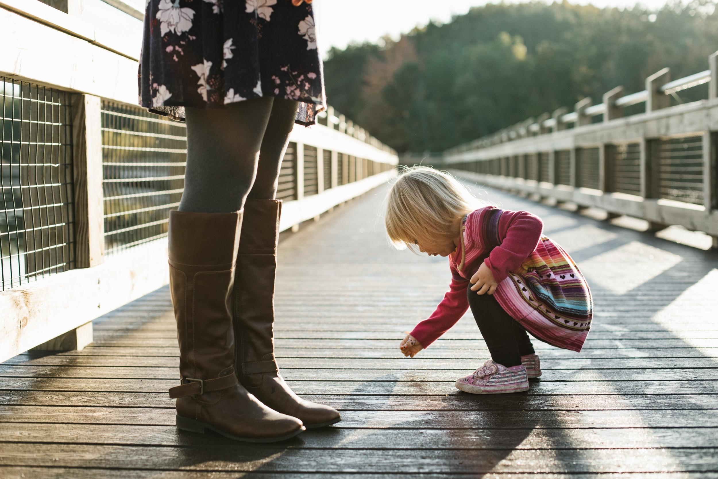 toddler picking something up from bridge