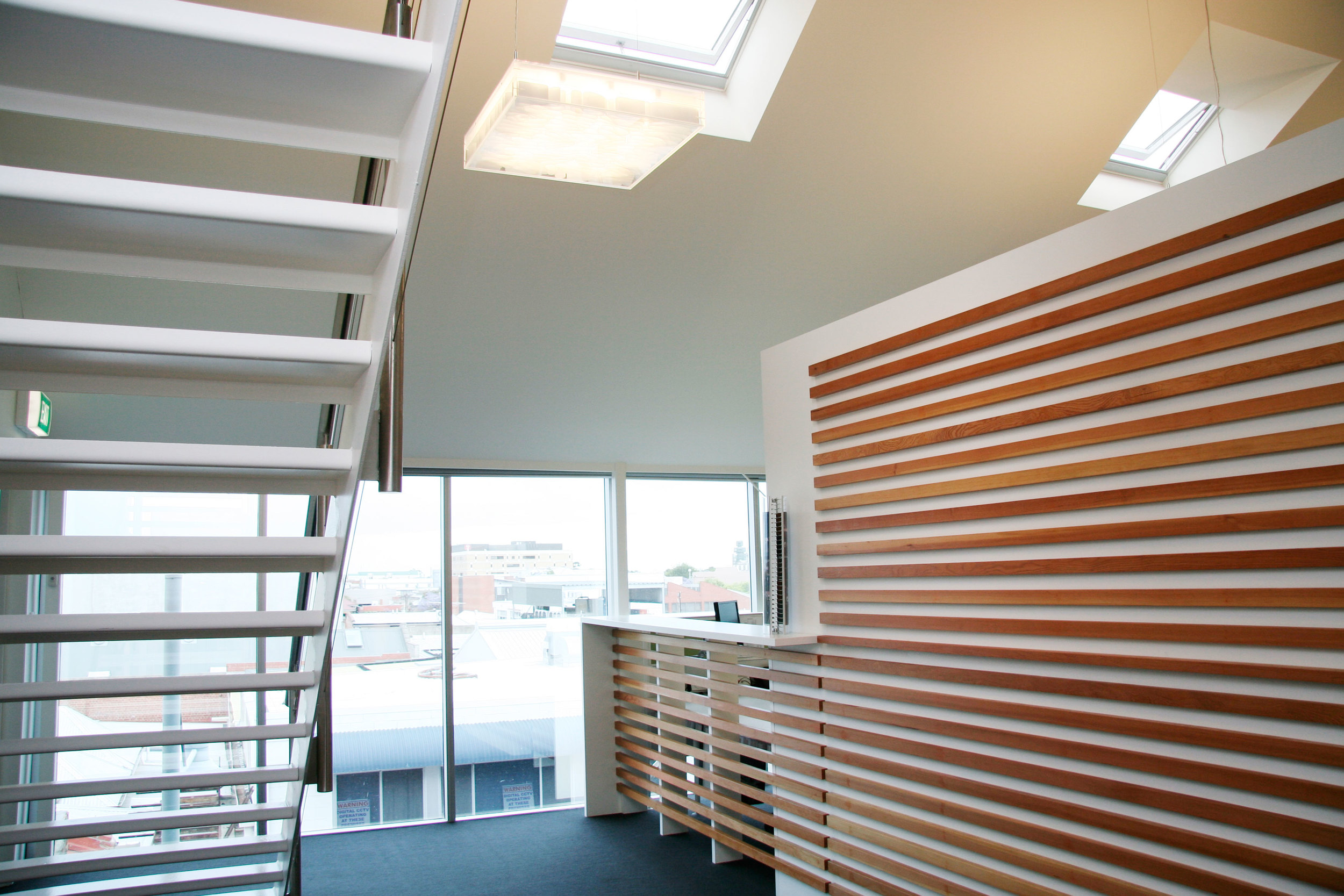 Skylights and Western-city views bounceoff a timber feature wall to welcome visitors to the office