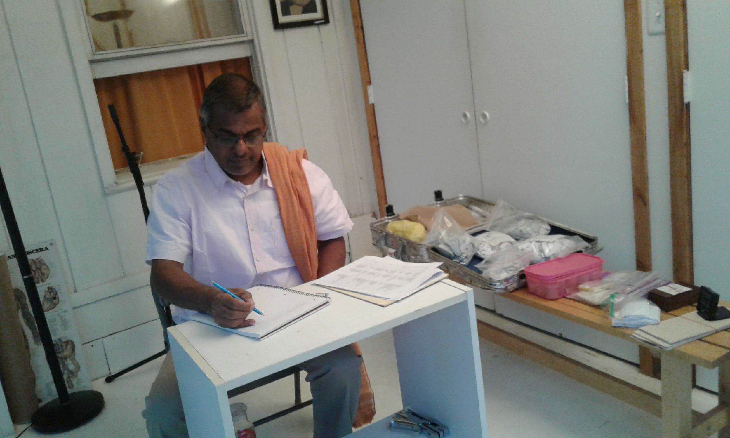 The Vaidyan Making Consultation Notes at the Ashram