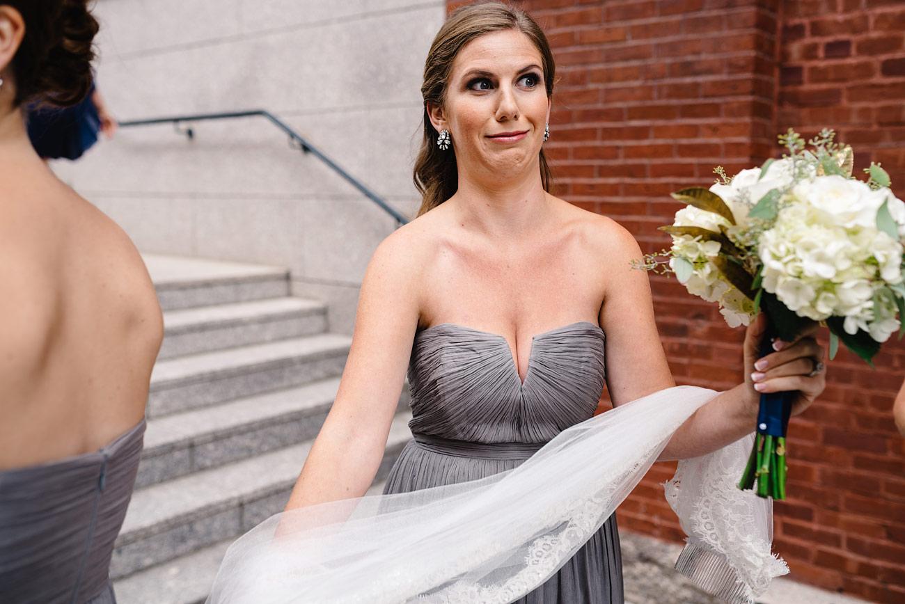 fun bridesmaid holding brides vail at st. cecilia church