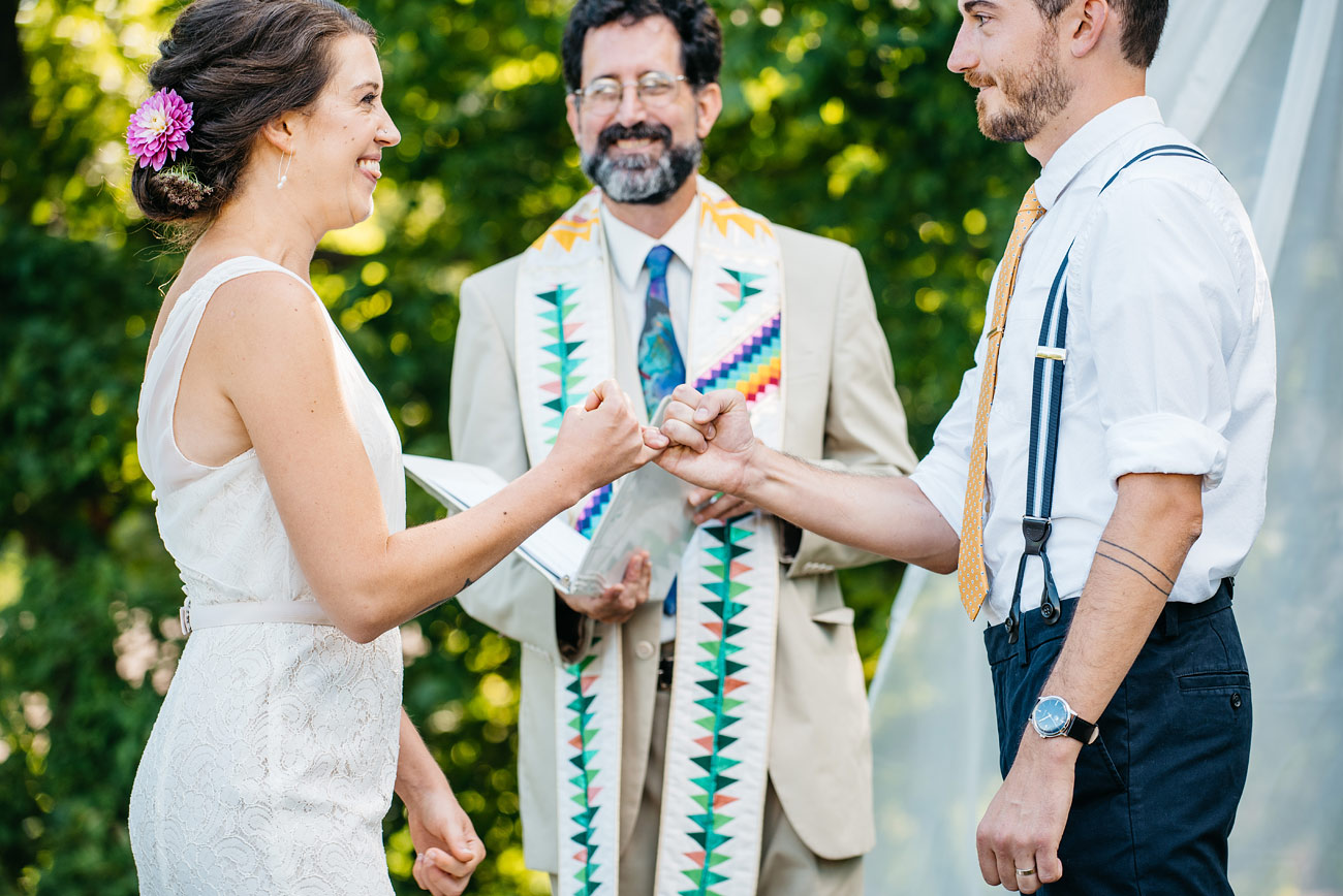 bride and groom pinky swear during their backyard new england ceremony creative and fun wedding photography