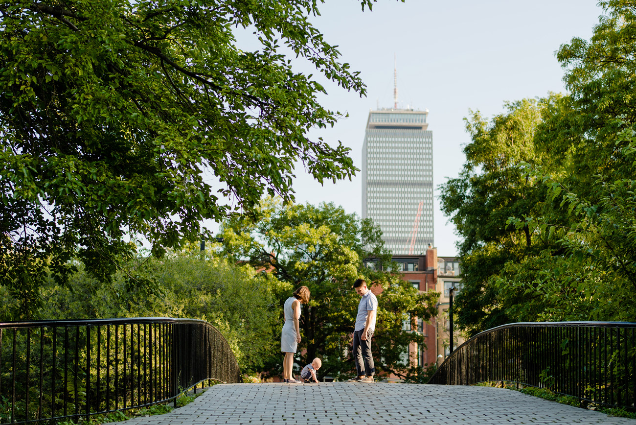 boston family photographer family having fun on bridge with views of prudential building