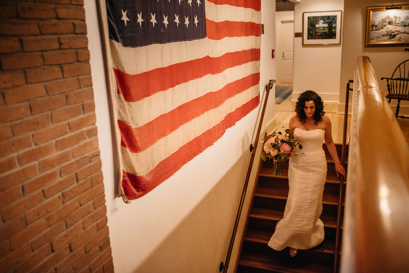 bride getting ready for the ceremony at thte pitcher inn in warren vt next to an american flag