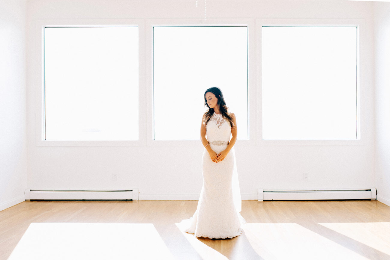 beautiful bride standing in window at belle mer wedding venue