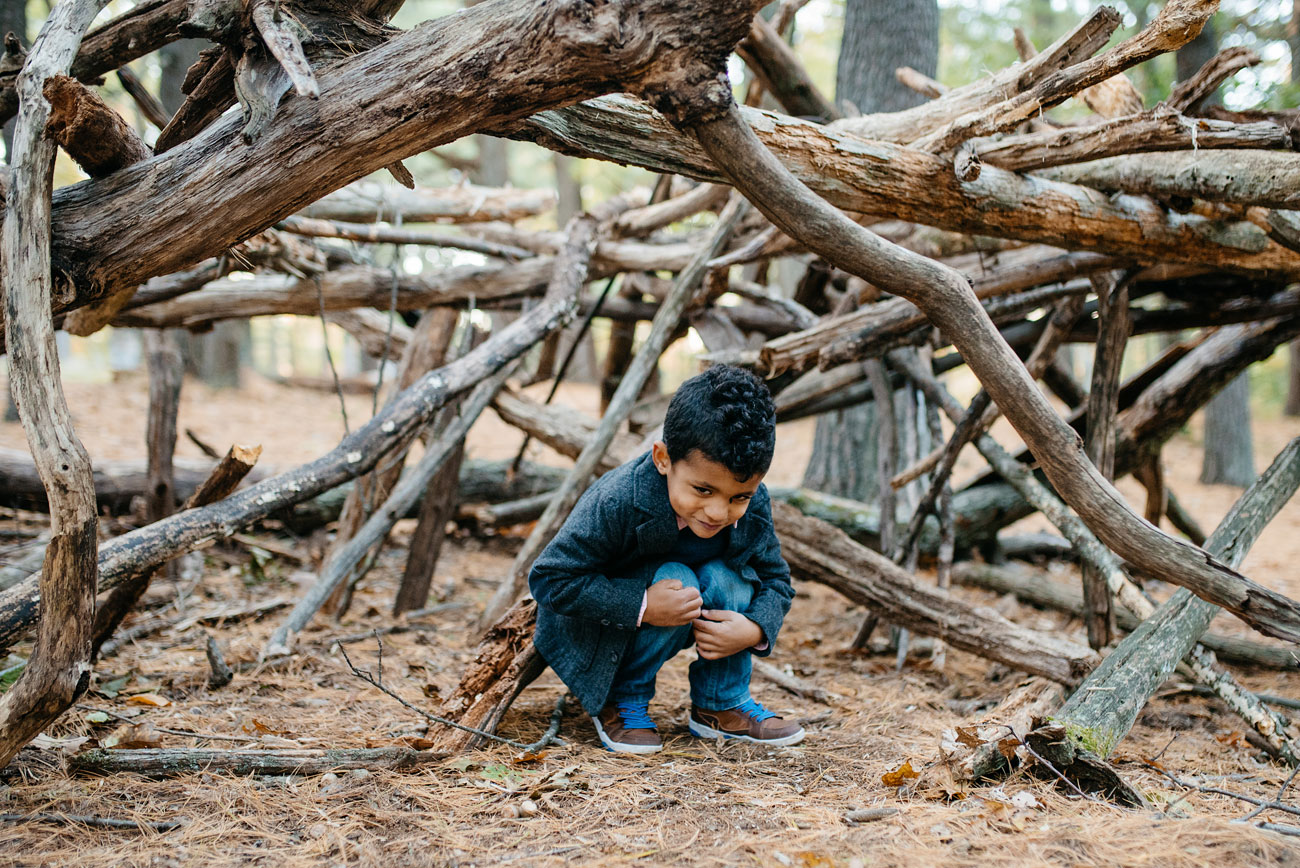 cute kid in a teepee made of sticks in the woods fun family photos