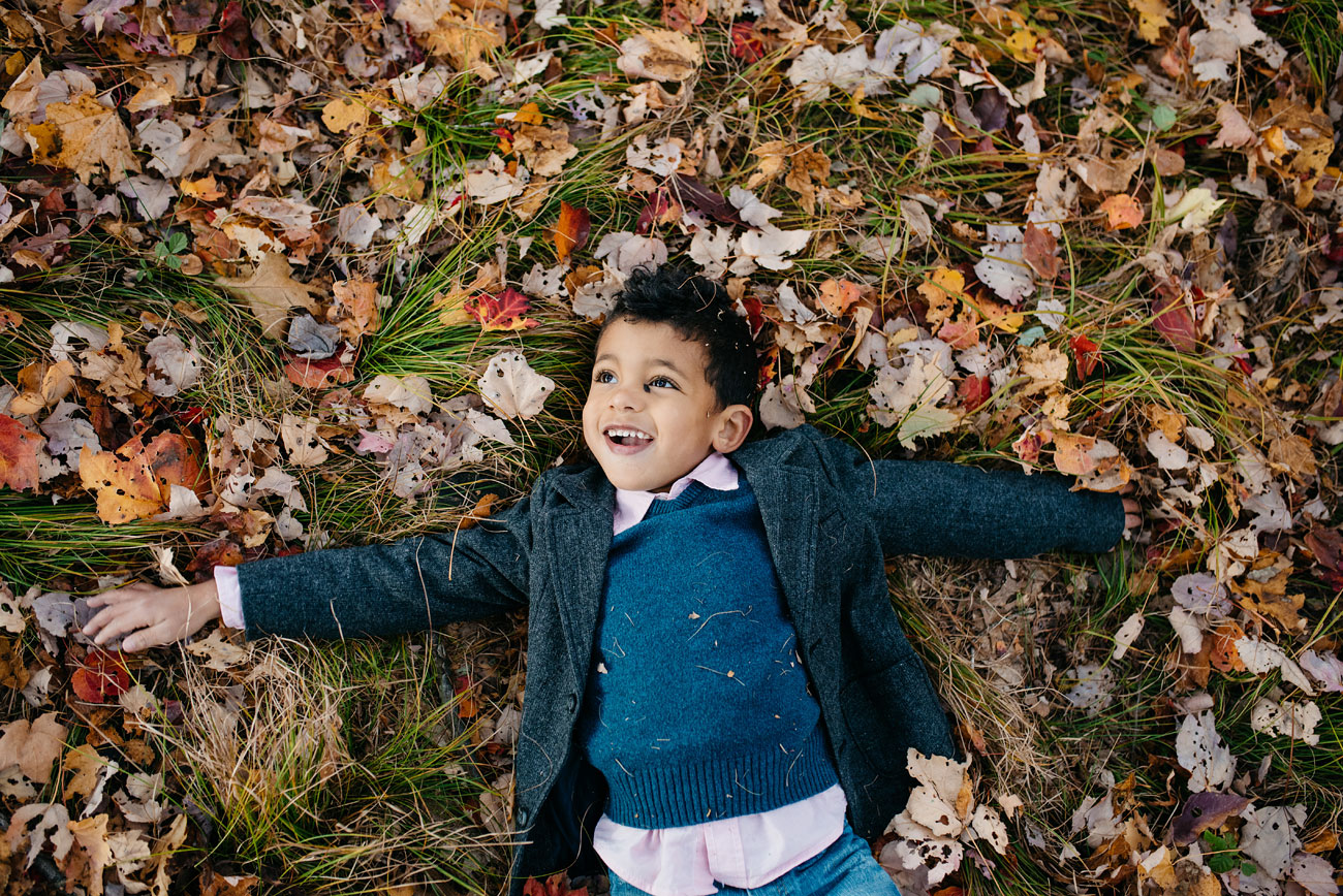 cute kid rolling in the leaves in fall during family session creative and fun boston family
