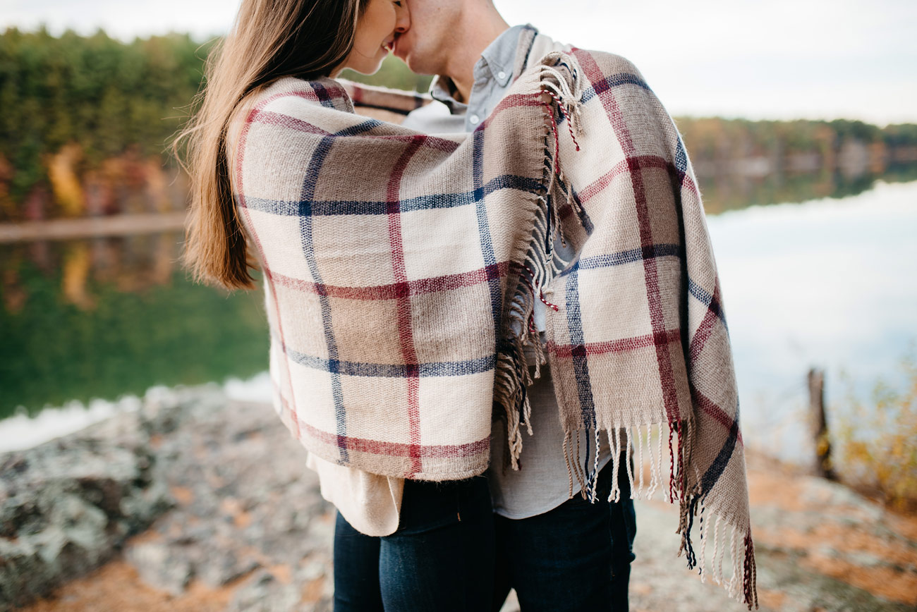 lifestyle couple snuggling in a blanket in boston middlesex fells reservation