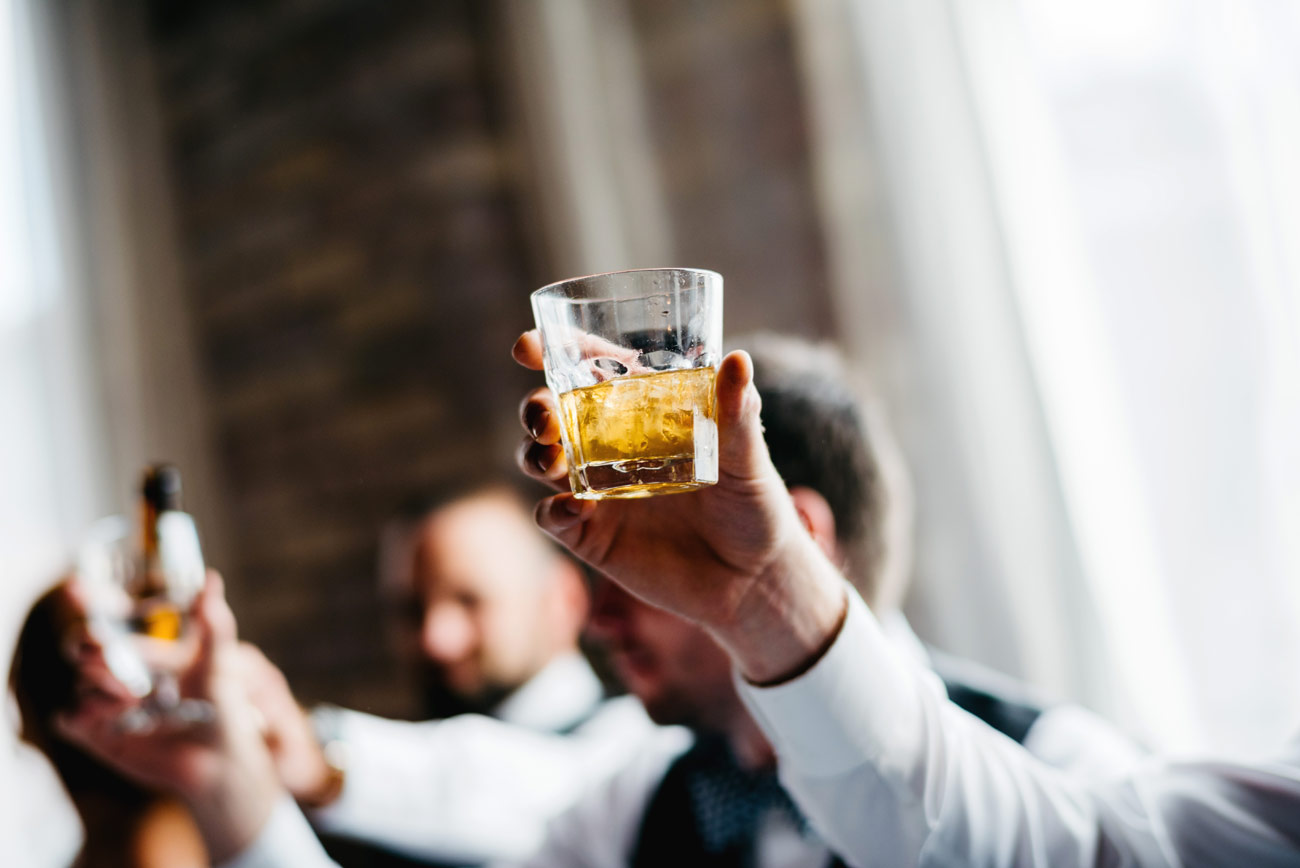 eve at the b.o.b. in michigan cheers and toast by the groomsmen holding a glass of whisky photography