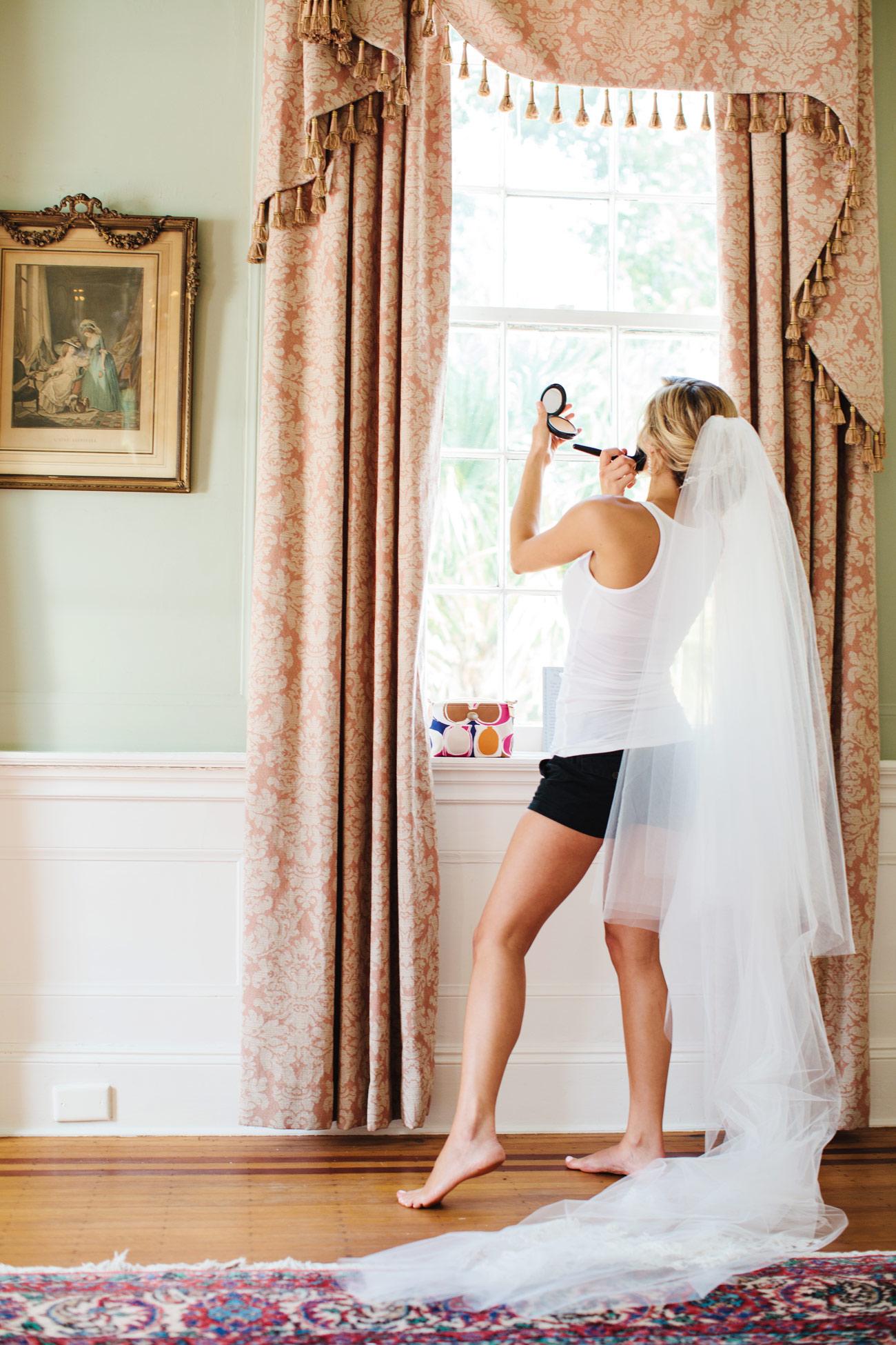 bride getting ready for a wedding at the lowndes grove plantation in charleston, sc destination charleston weddings