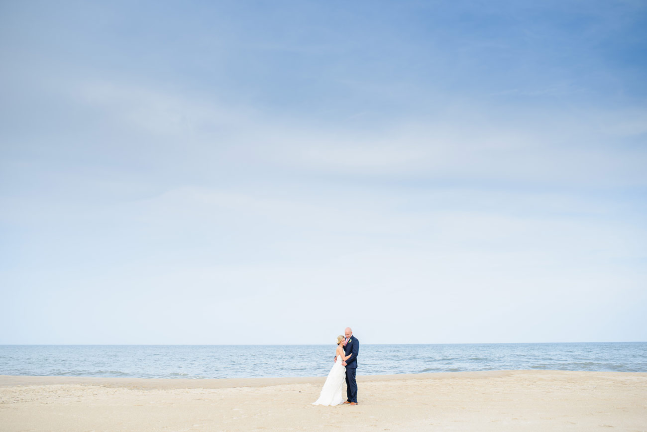 bride and groom on bethany beach with the open sky and ocean