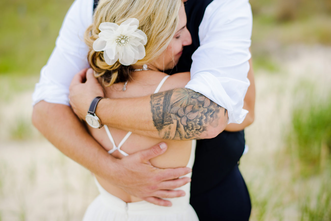 groom with tattoo hugging his bride on the beach
