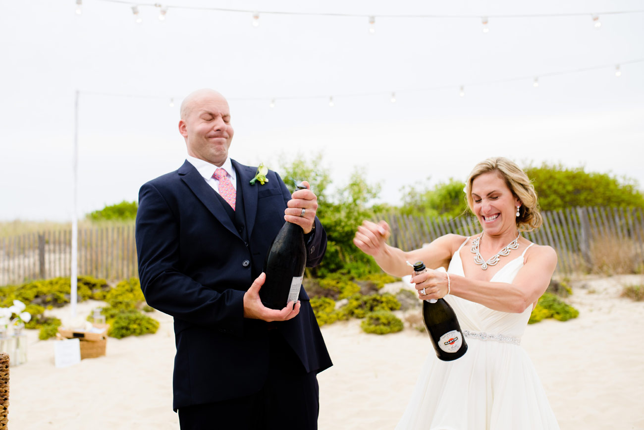 bride and groom with champagne at their private beach wedding