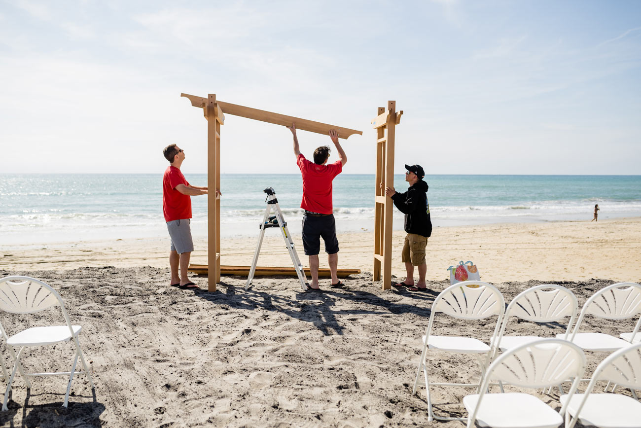 setting up the custom arbor on carlsbad beach at