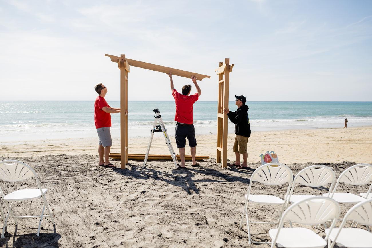 setting up the custom arbor on carlsbad beach at