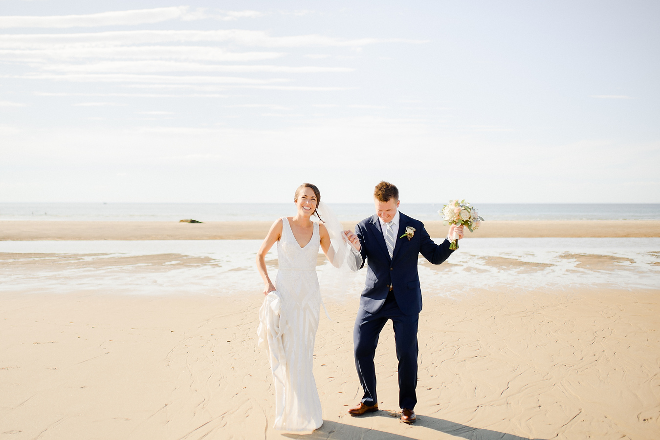 bride and groom having fun on the beach in cape cod