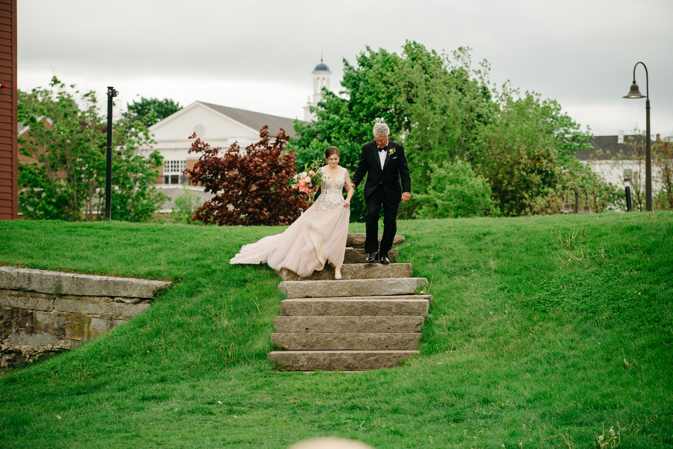 bride and father walking down to the ceremony at gibbet hill barn in groton, ma