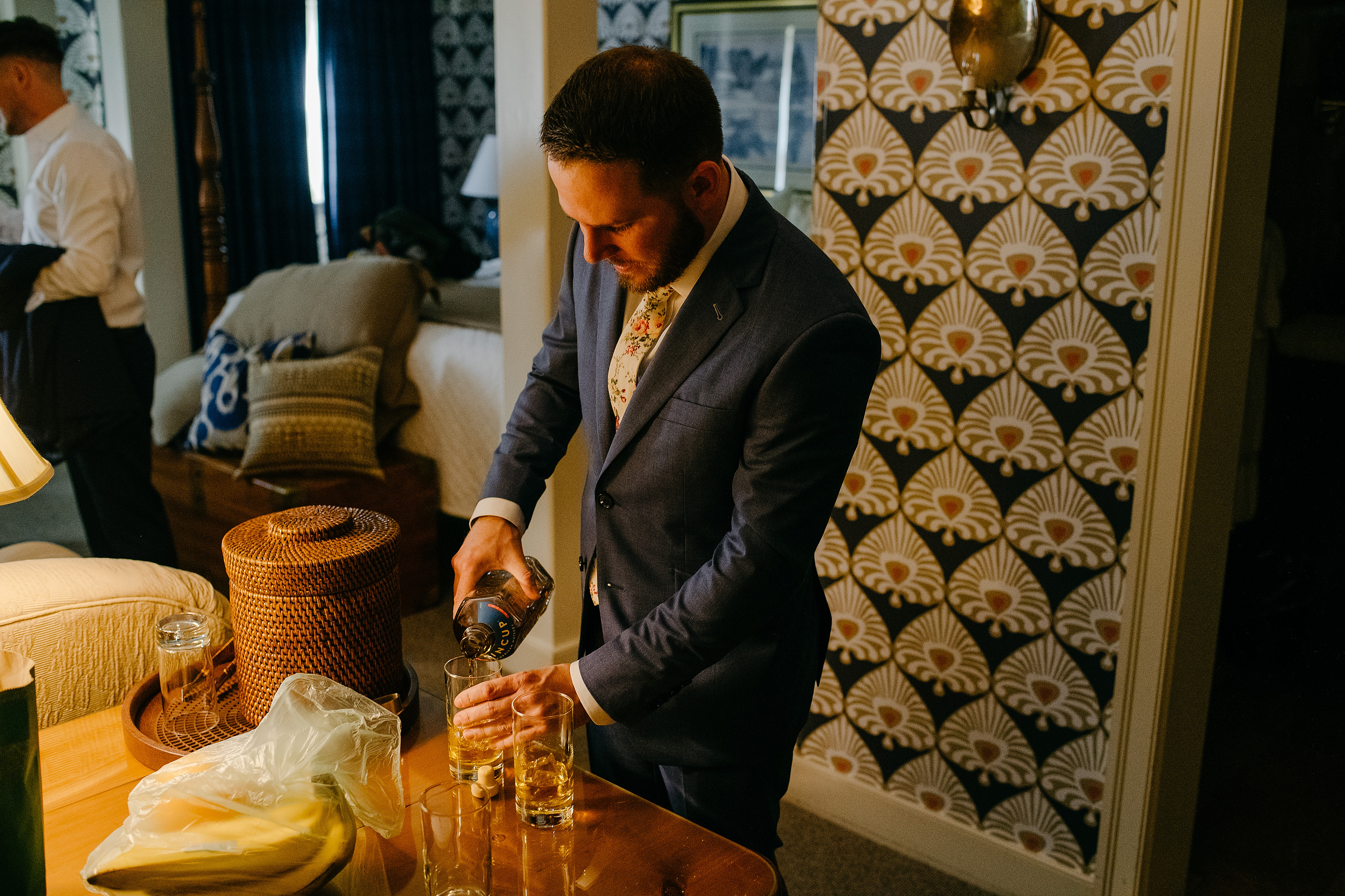 groom pouring a glass of whisky for his groomsmen