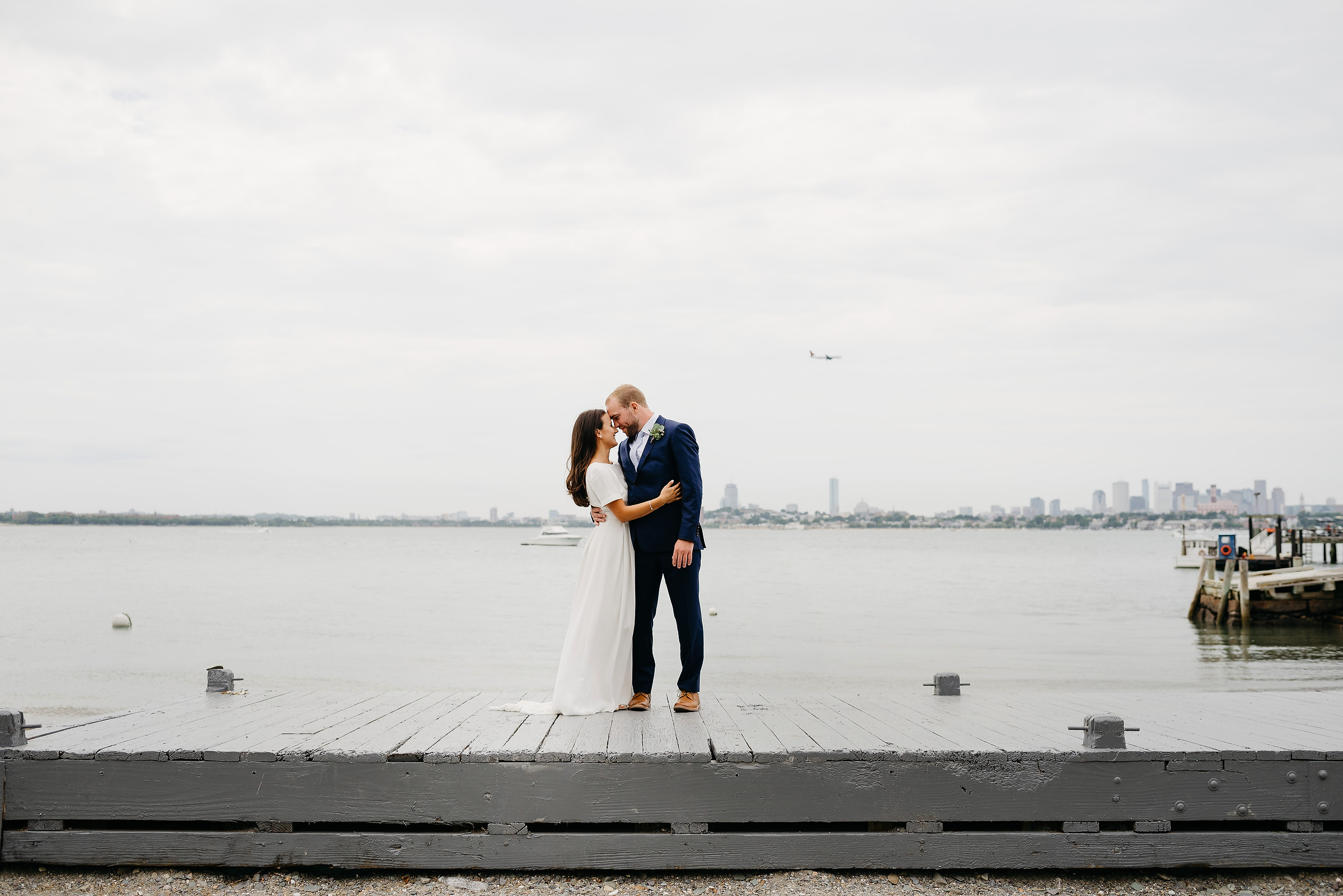 amazing thompson island wedding photo of boston skyline with couple kissing