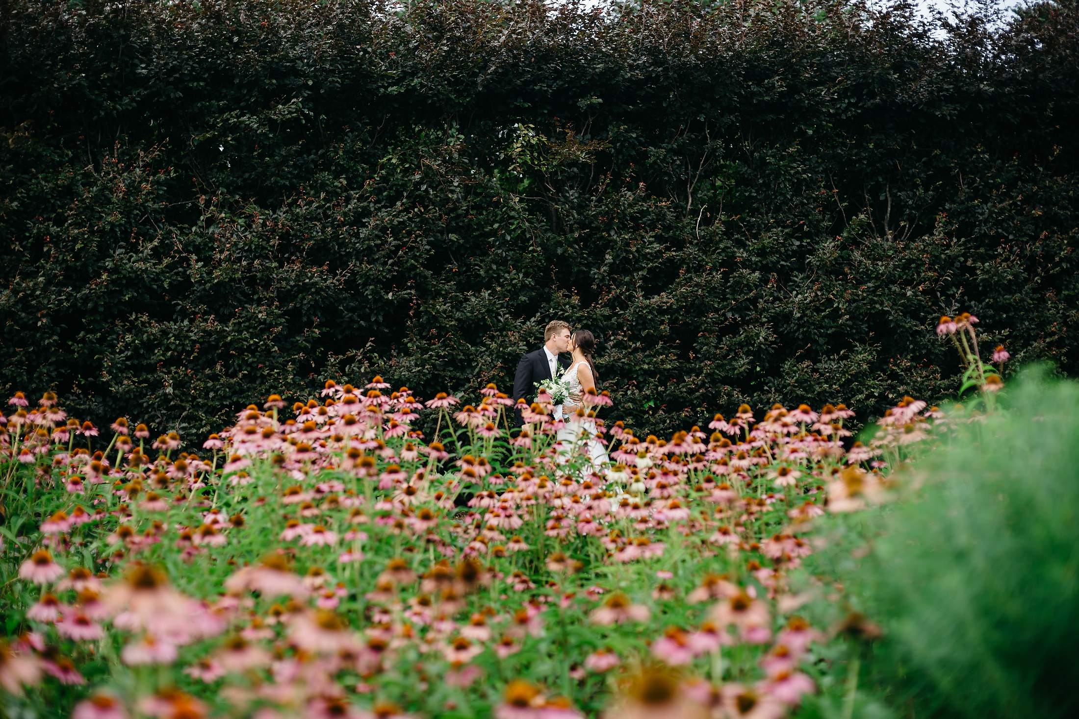 bride and groom in a field of flowers at elm banks summer wedding