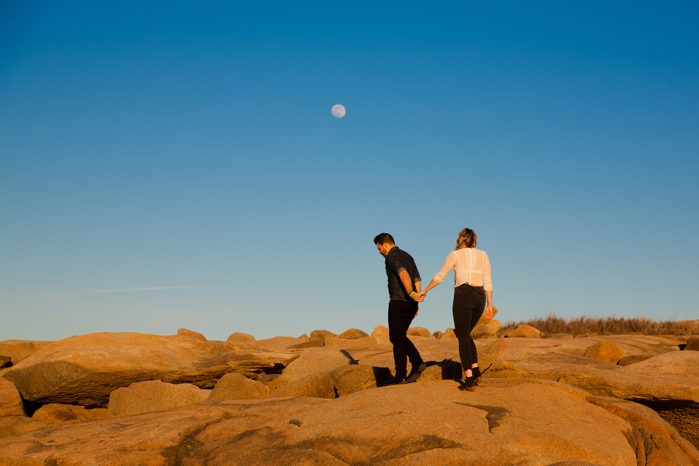 amazing boston engagement session location photos, couple walking on rocks