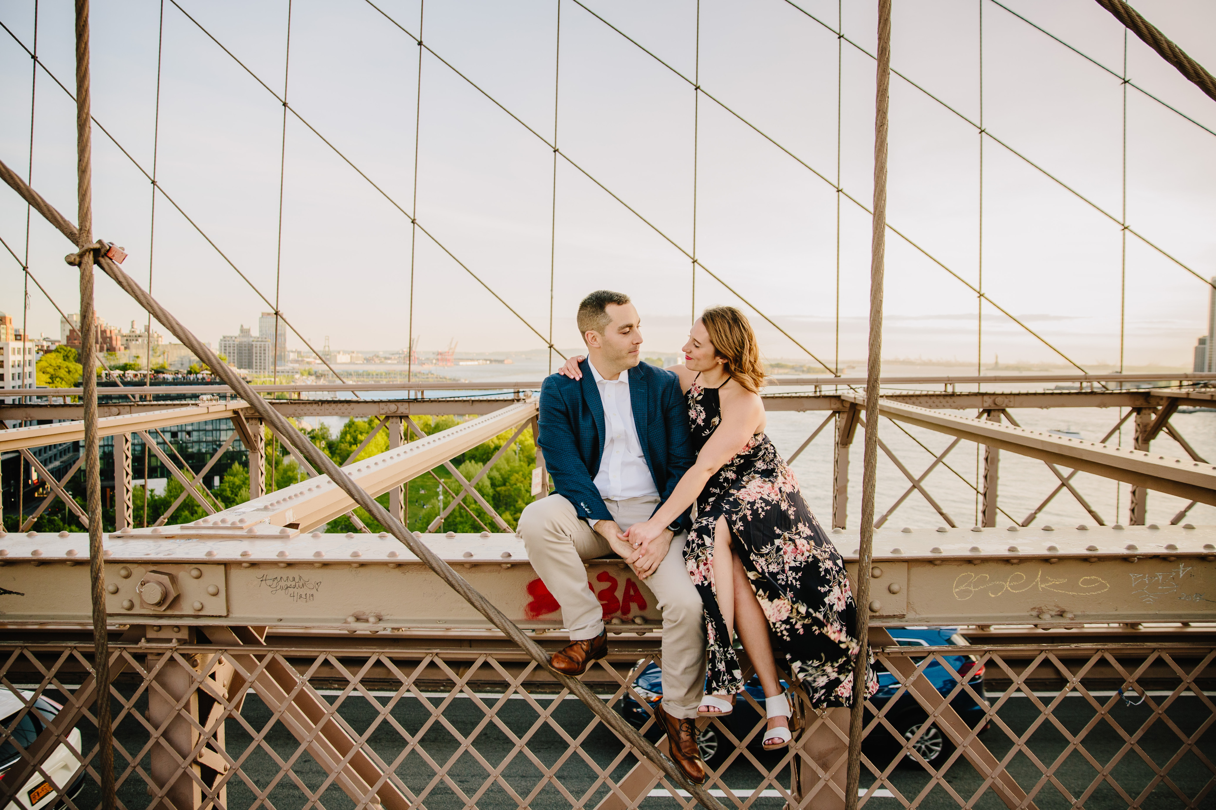 amazing portrait of couple sitting on the brooklyn bridge at their engagement session
