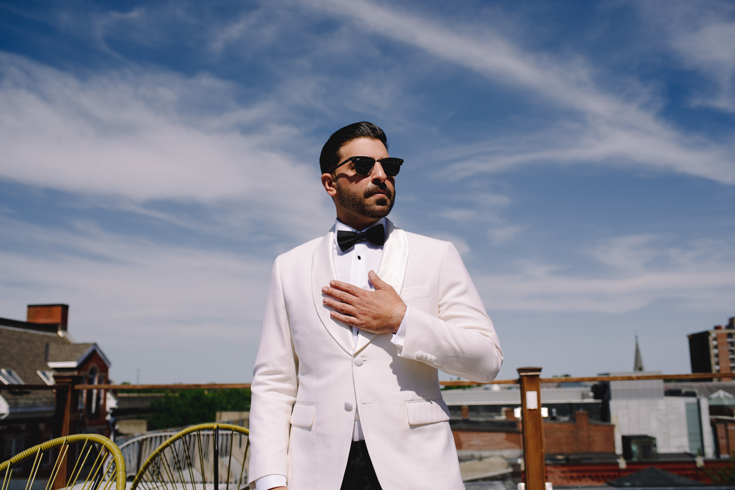 modern groom with white tux and black tie in nyc
