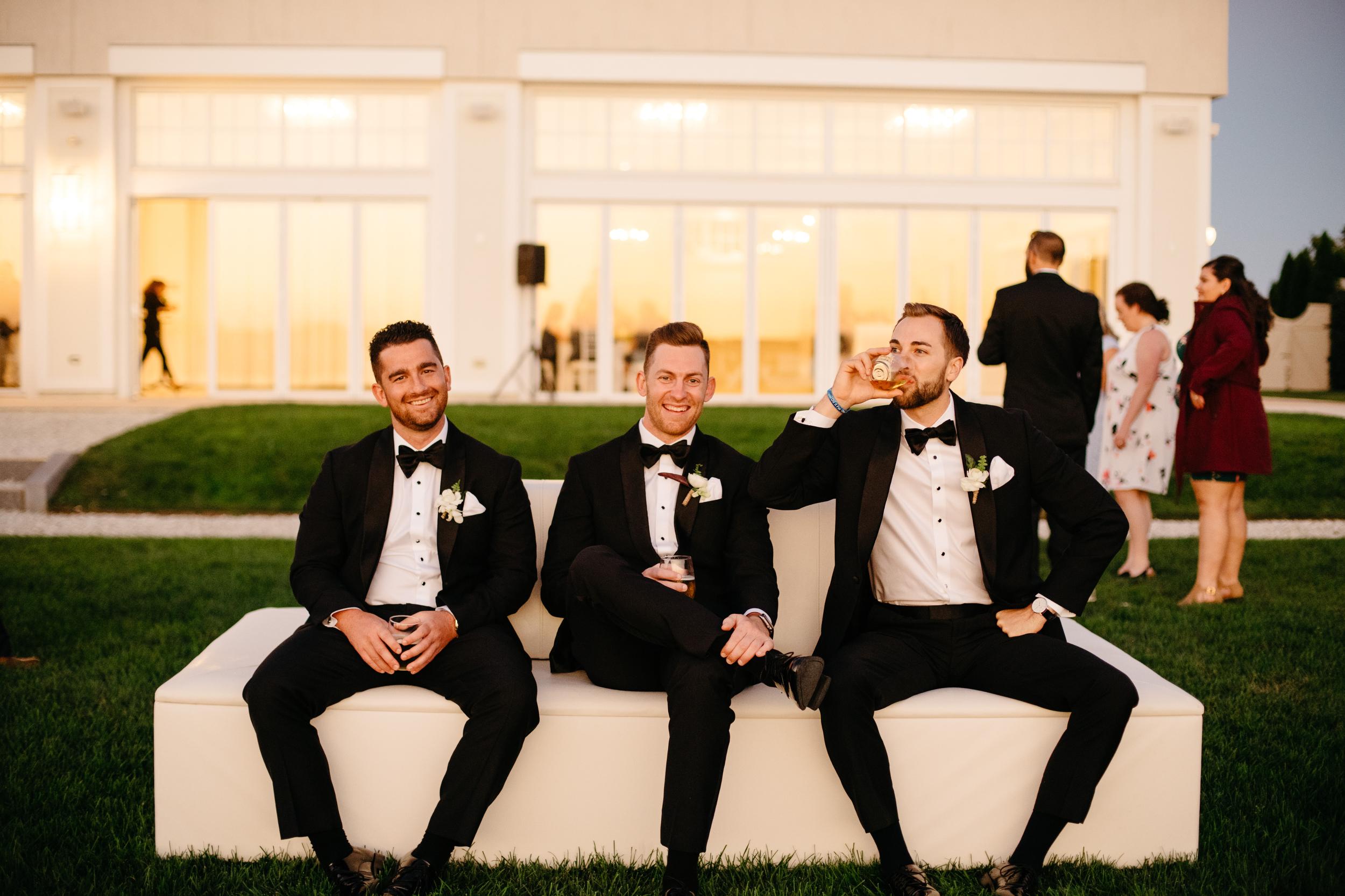 black tie groomsmen lounging at a classy ocean front venue in newport RI