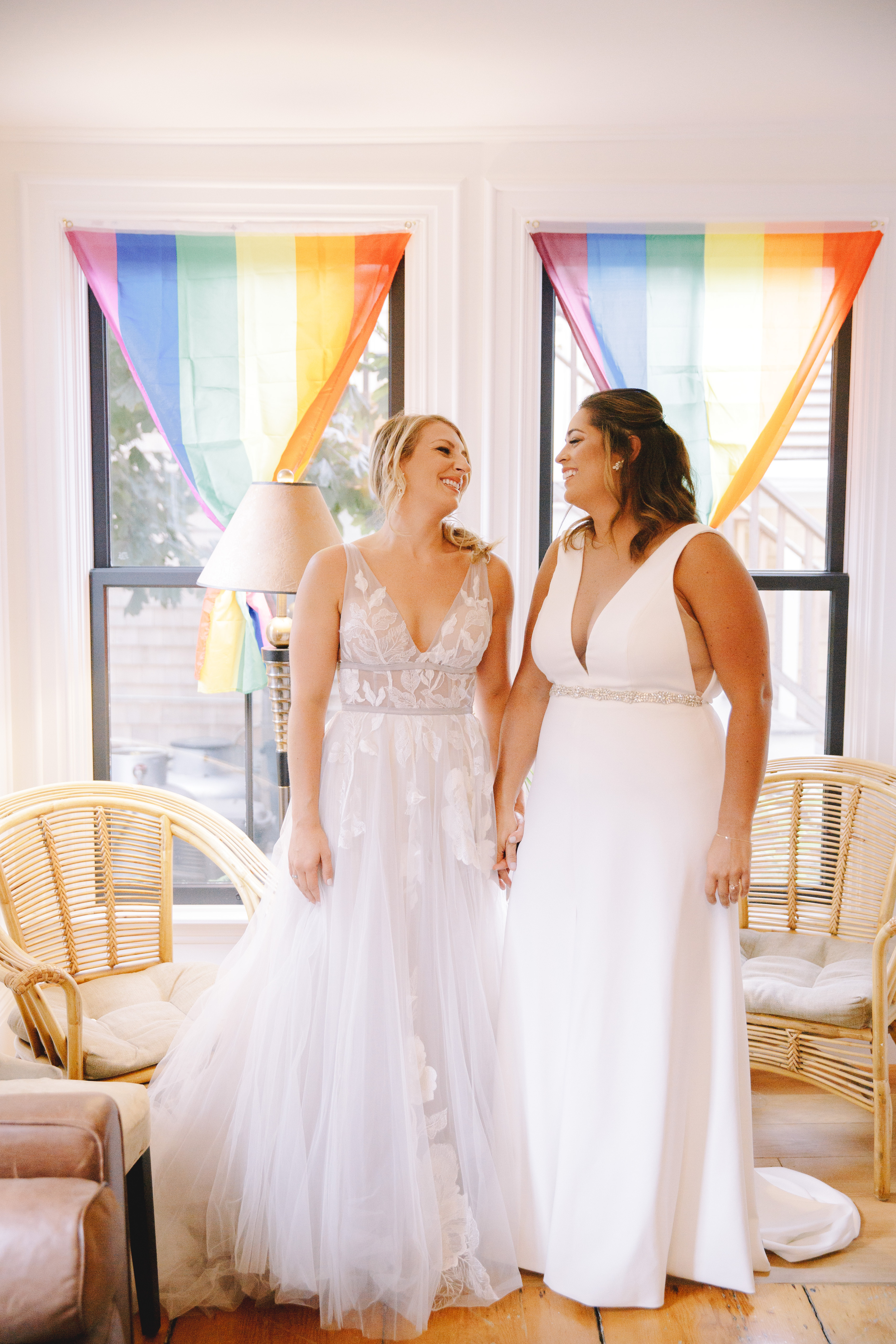 stunning brides with rainbow flags standing inside the waterford inn in provincetown at their wedding