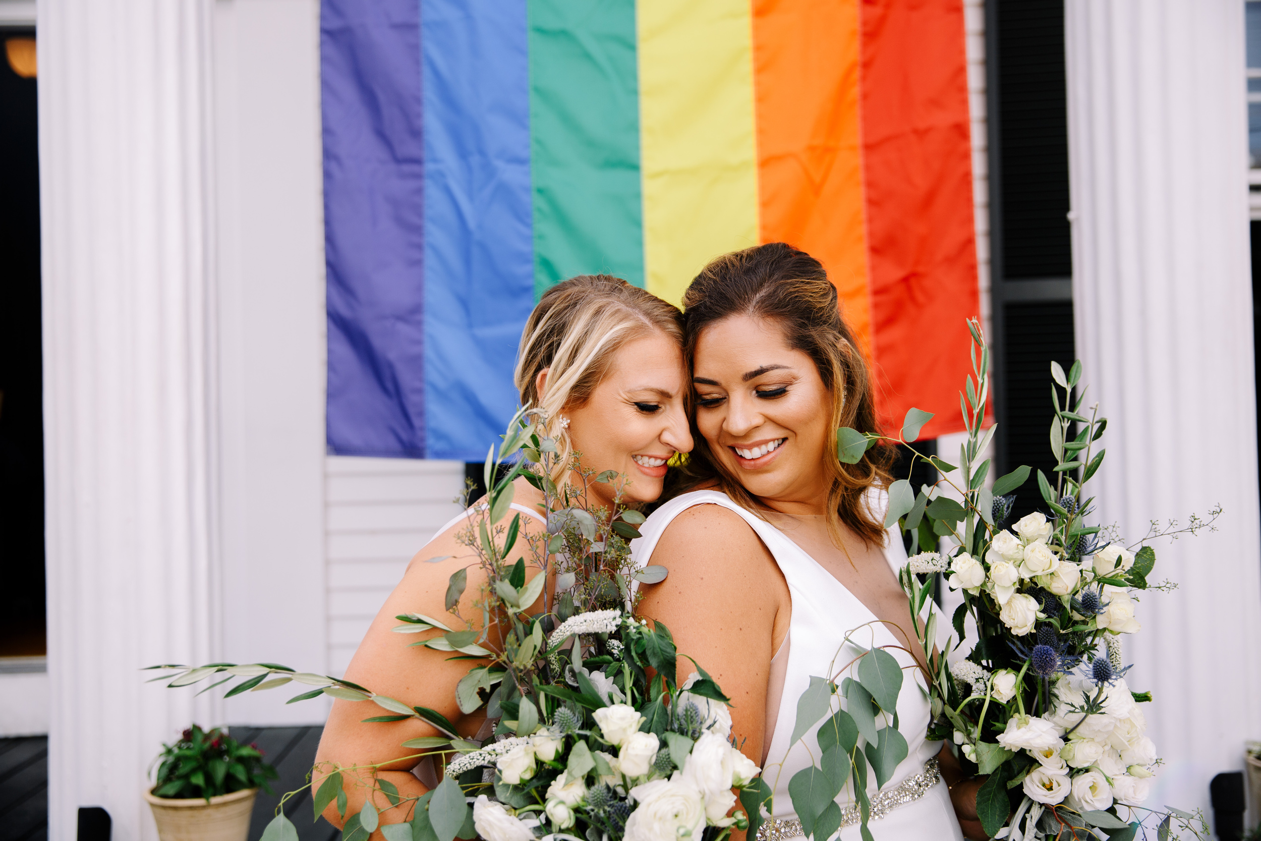 two gorgeous brides in front of rainbow flag at their strangers and saints wedding in downtown provincetown