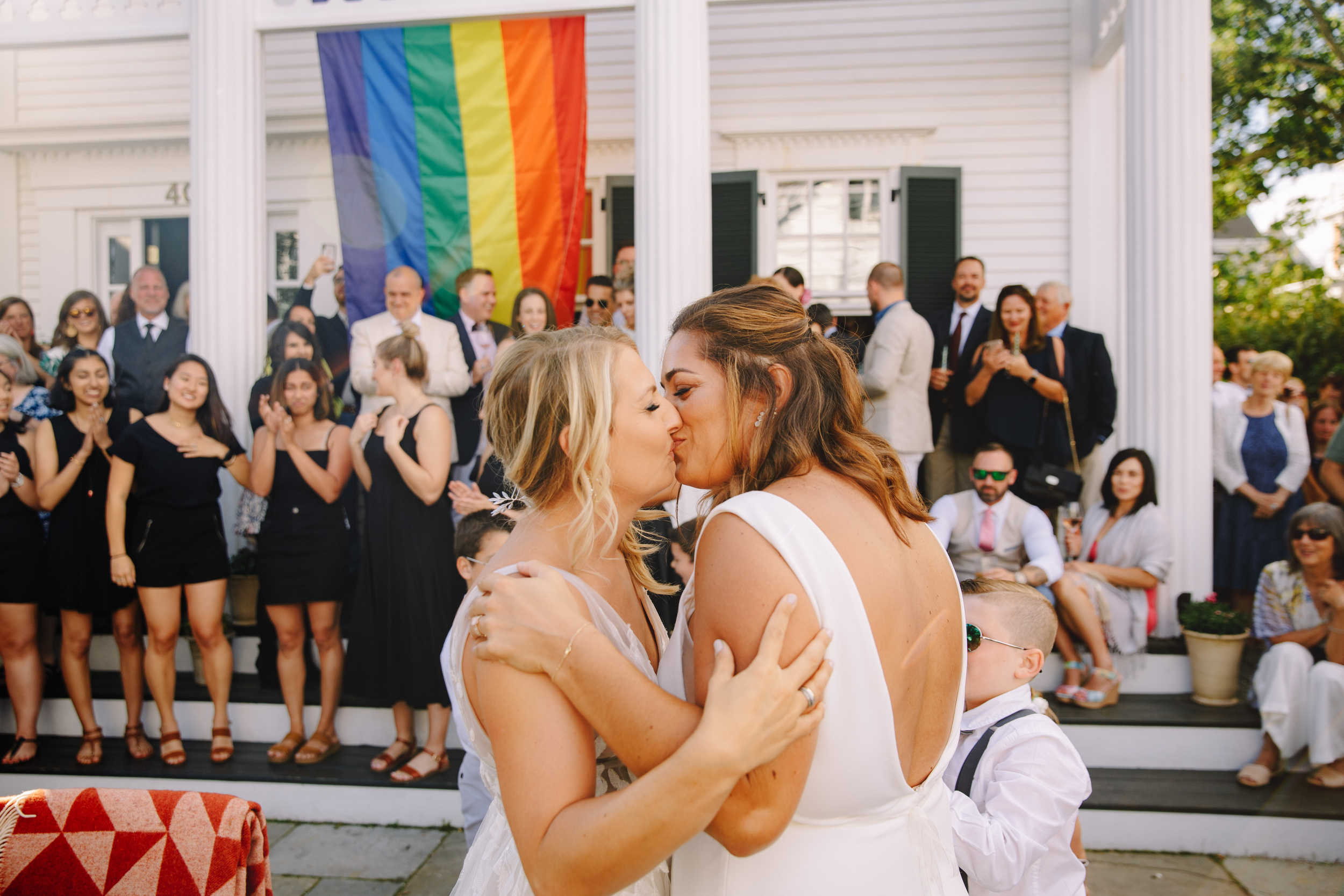 provincetown summer wedding at strangers and saints outdoor shot of brides kissing