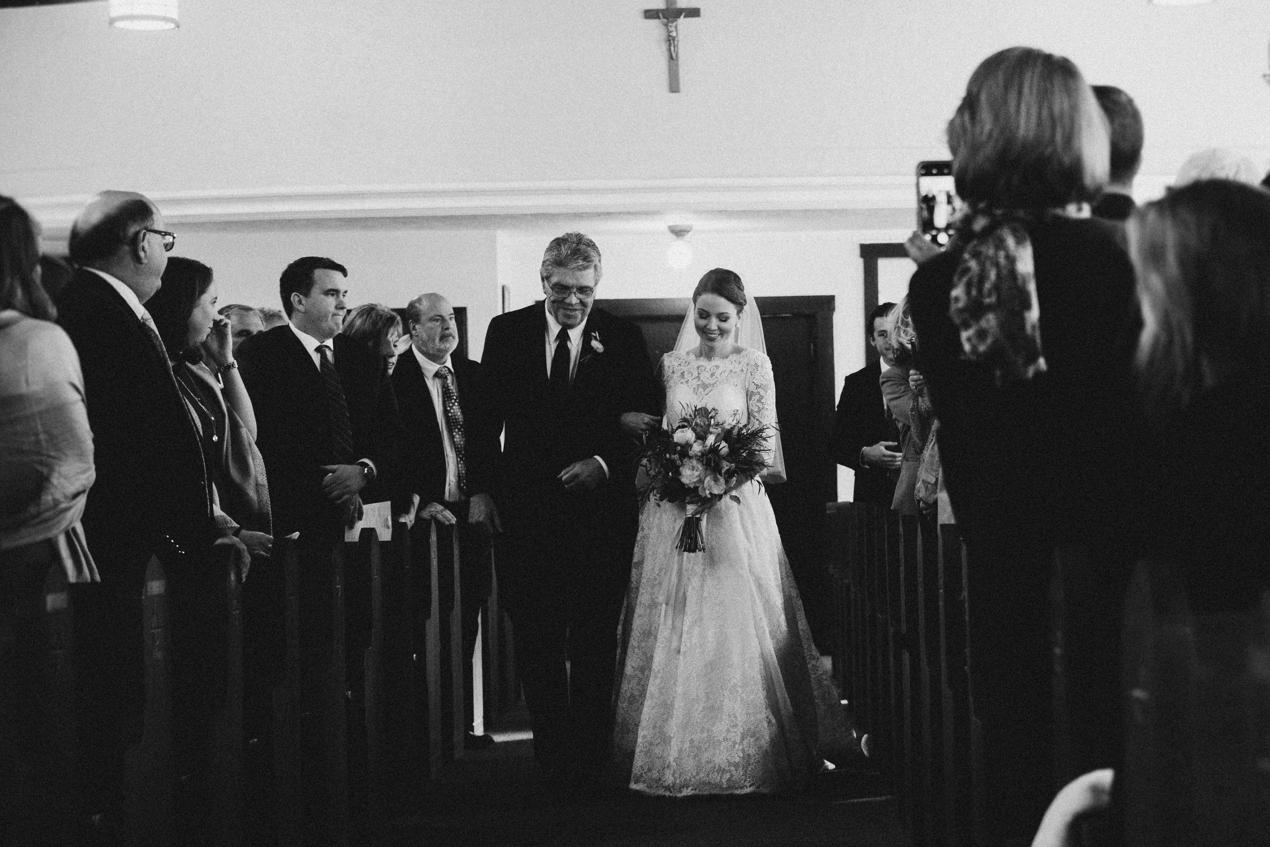 bride with her dad walking in to the wedding at st. james classic church in groton timeless celebrity wedding