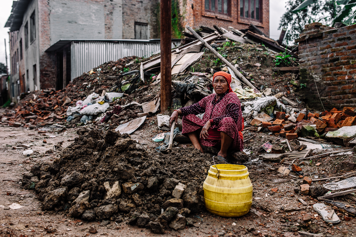A woman gathers the dirt and mix it with water to create material needed to rebuild her home. Assistance from the government to rebuild the destroyed homes have been slow and inefficient.  Sankhu, Nepal   2015