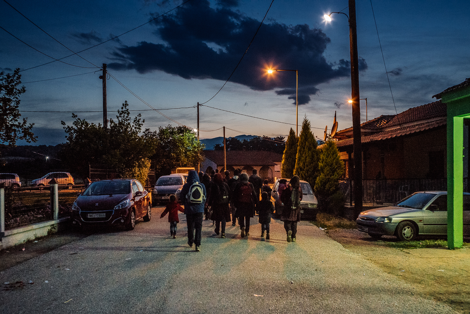 A family of asylum seekers making one last attempt to cross the border into Macedonia in the cover of darkness before being forced to relocate to official camps. Idomeni, Greece, 2016