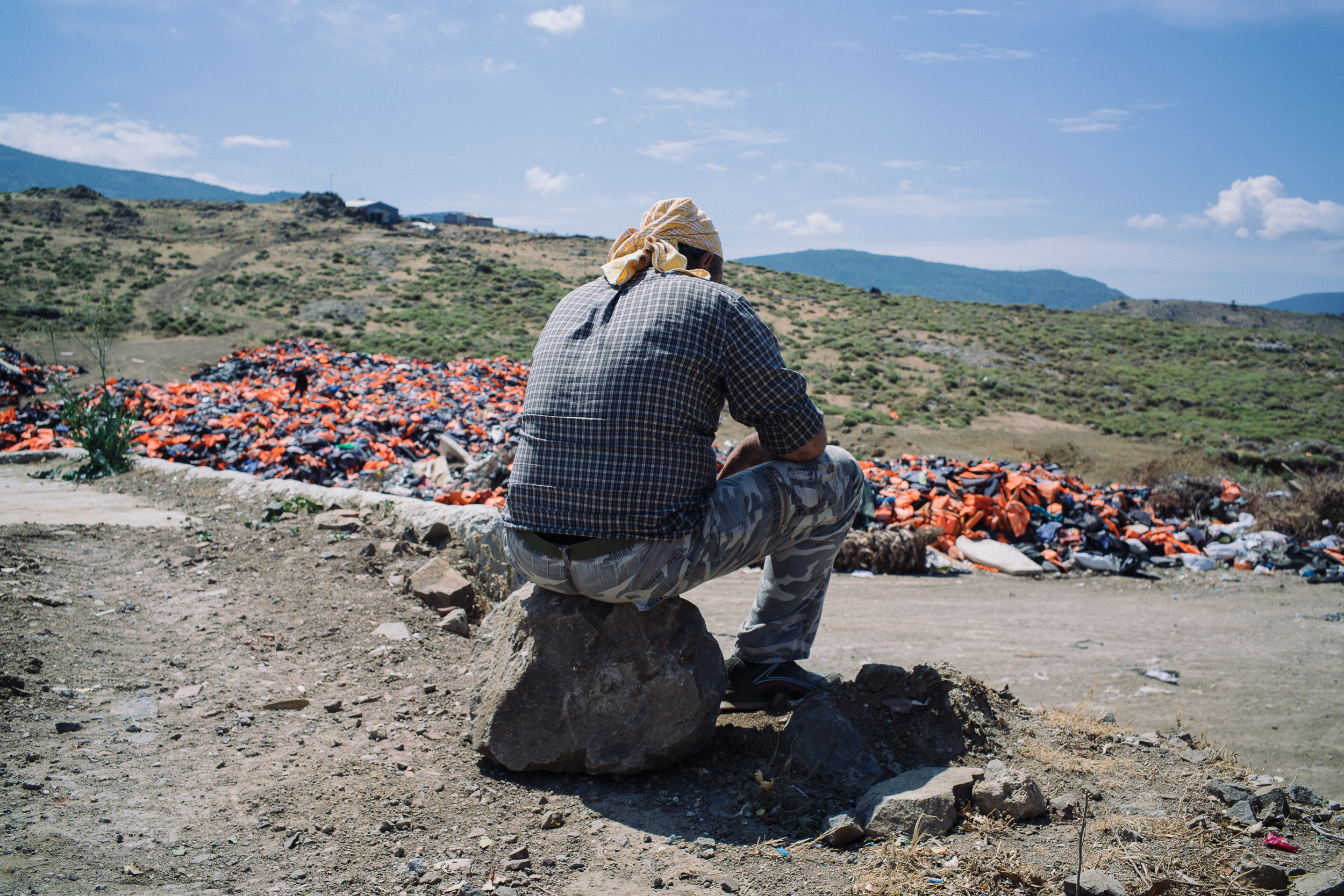 A local caretaker of the life vest cemetery waits in the blazing heat for the next arrival of trucks carrying discarded life vests from the shores to Molyvos.