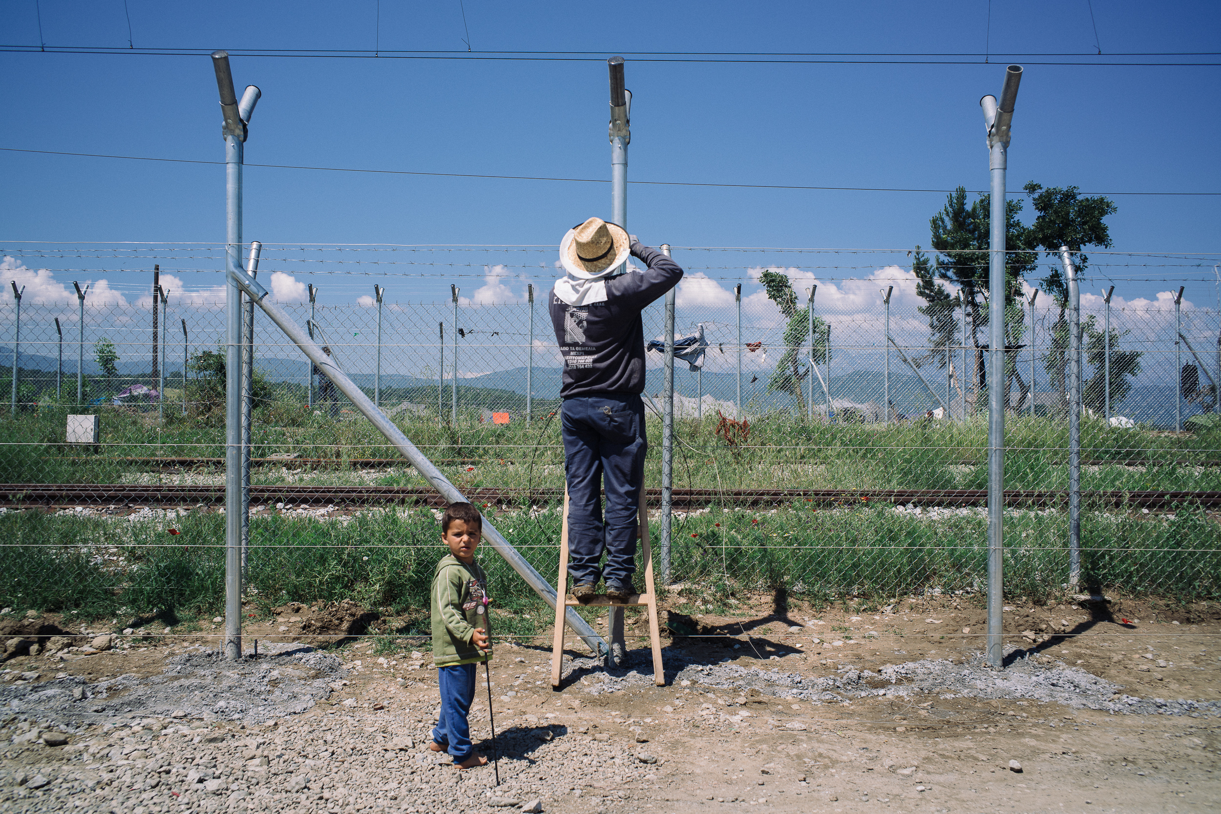 A young Syrian boy innocently watches a man fixing the fence that separates Greece and Macedonia in Idomeni camp.