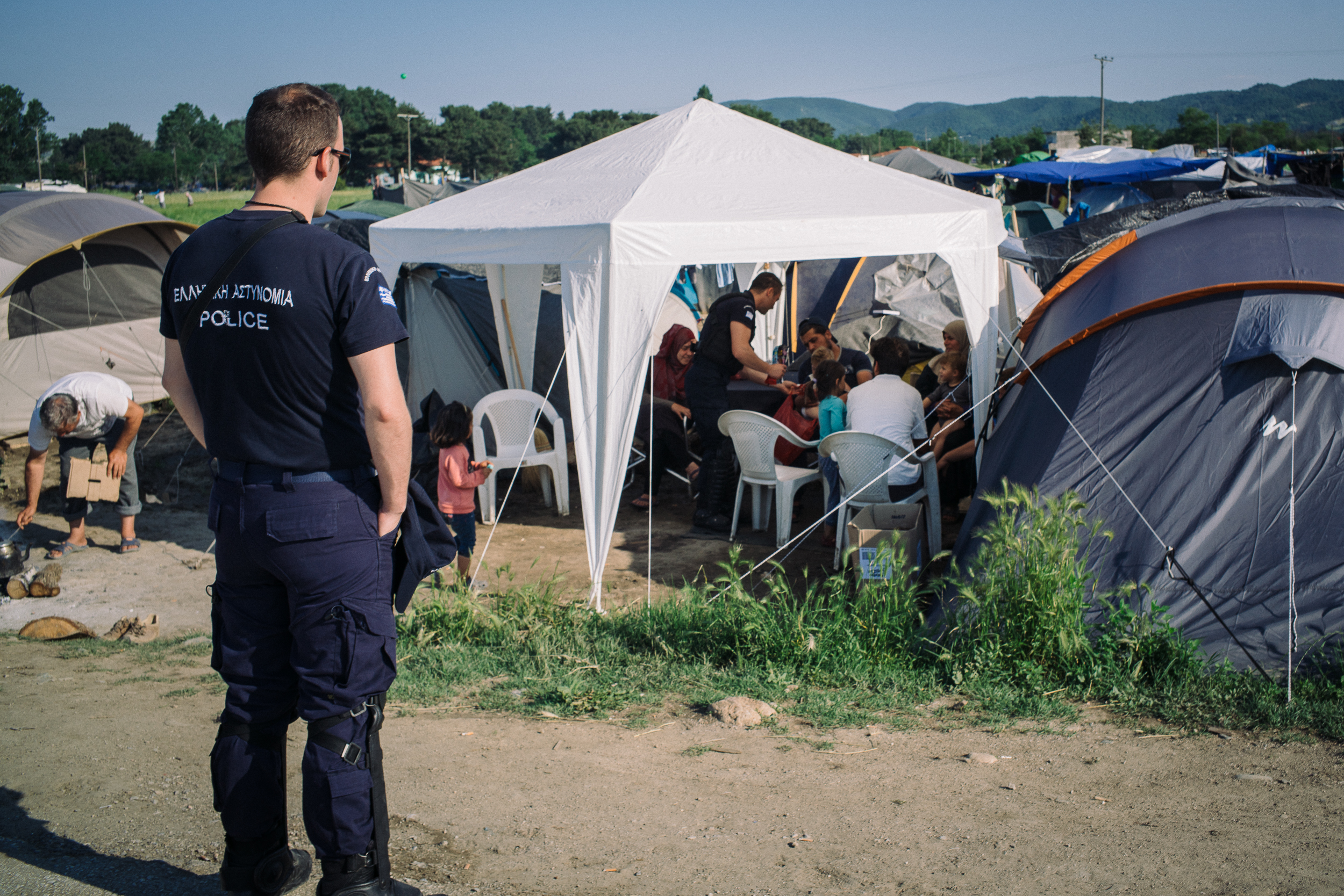 Two police officers bought sweet treats to give out to the children as they went around the camp informing the asylum seekers that they will all be relocated to official government camps the next day.